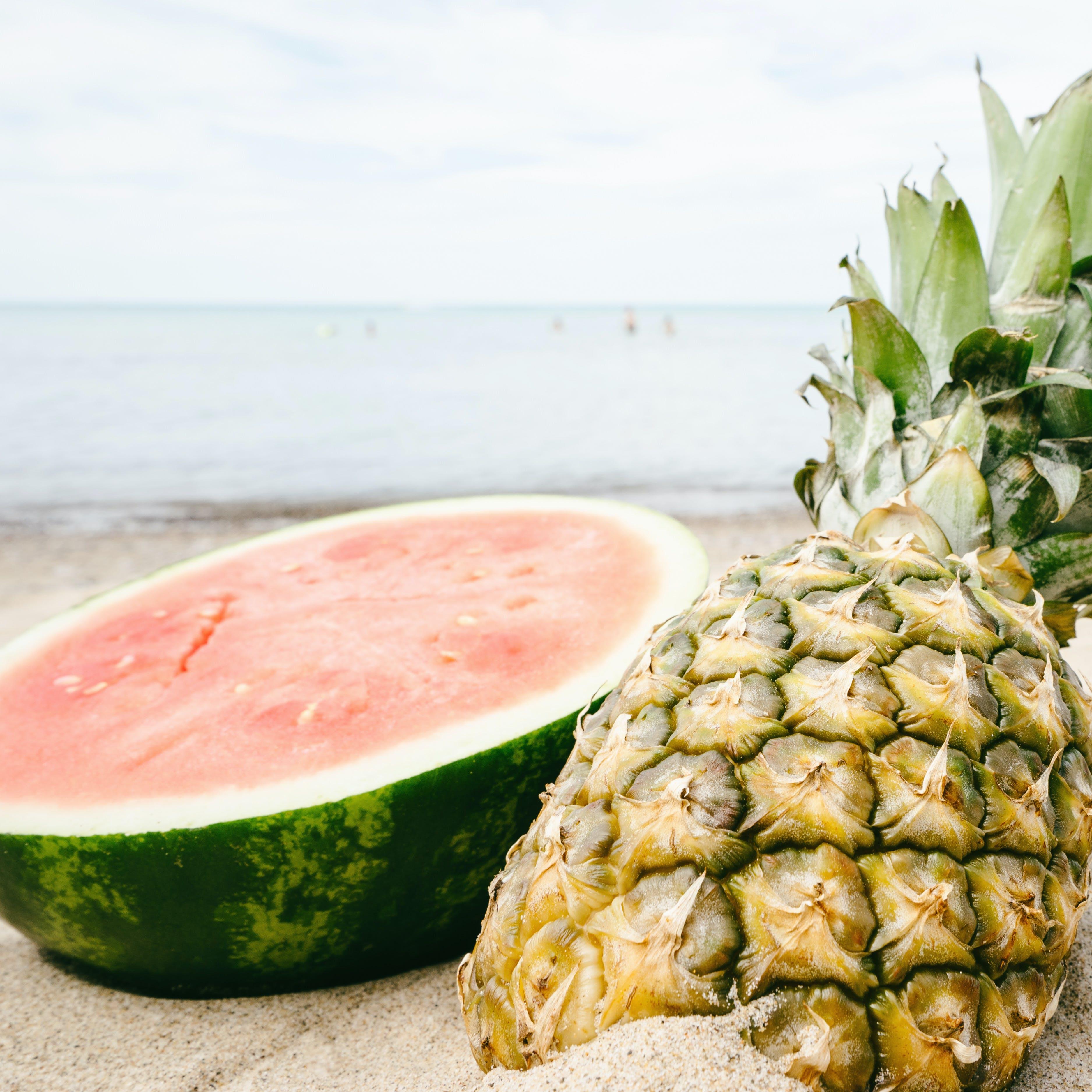 Sliced Watermelon and Pineapple Near Seashore