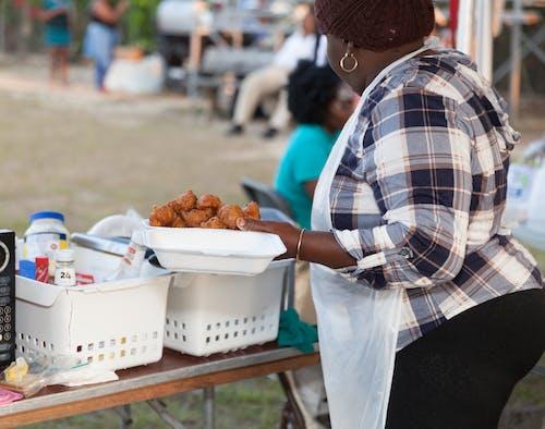 Gratis lagerfoto af dame holder, ø-stegte conch fritters