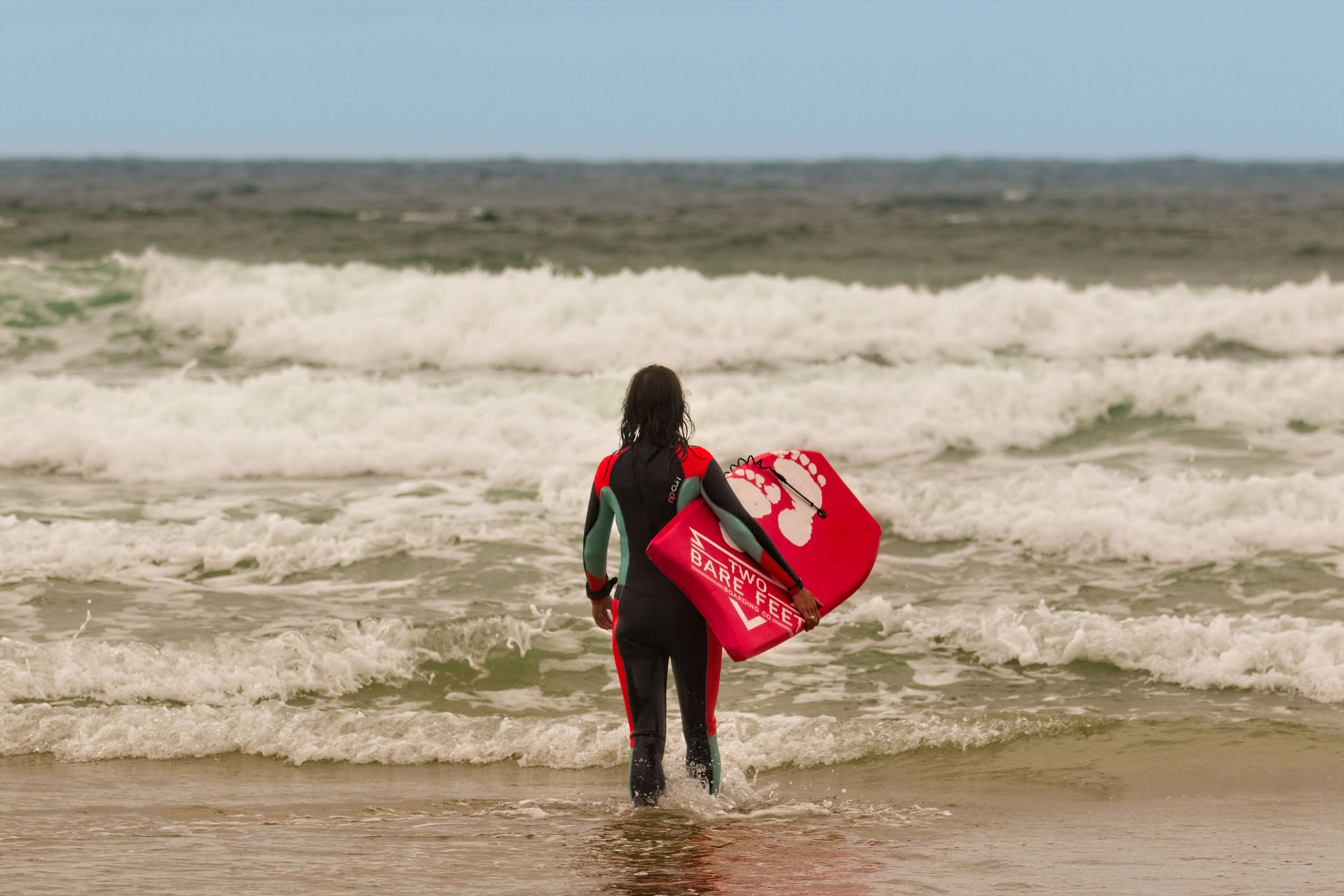 Person Standing on Sea Shore Holding Body Board