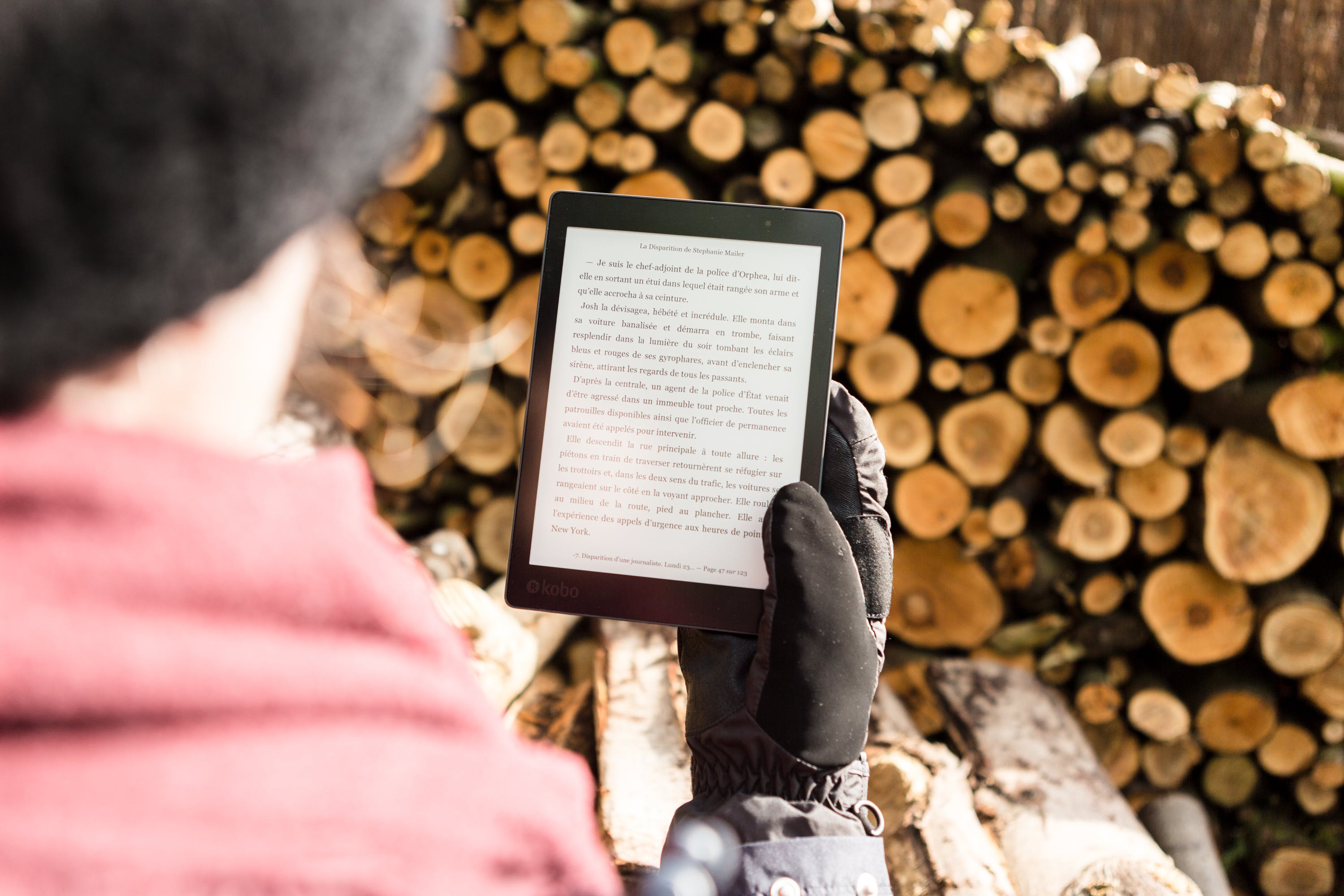 Person Holding Black E-book Reader Near Pile of Firewood