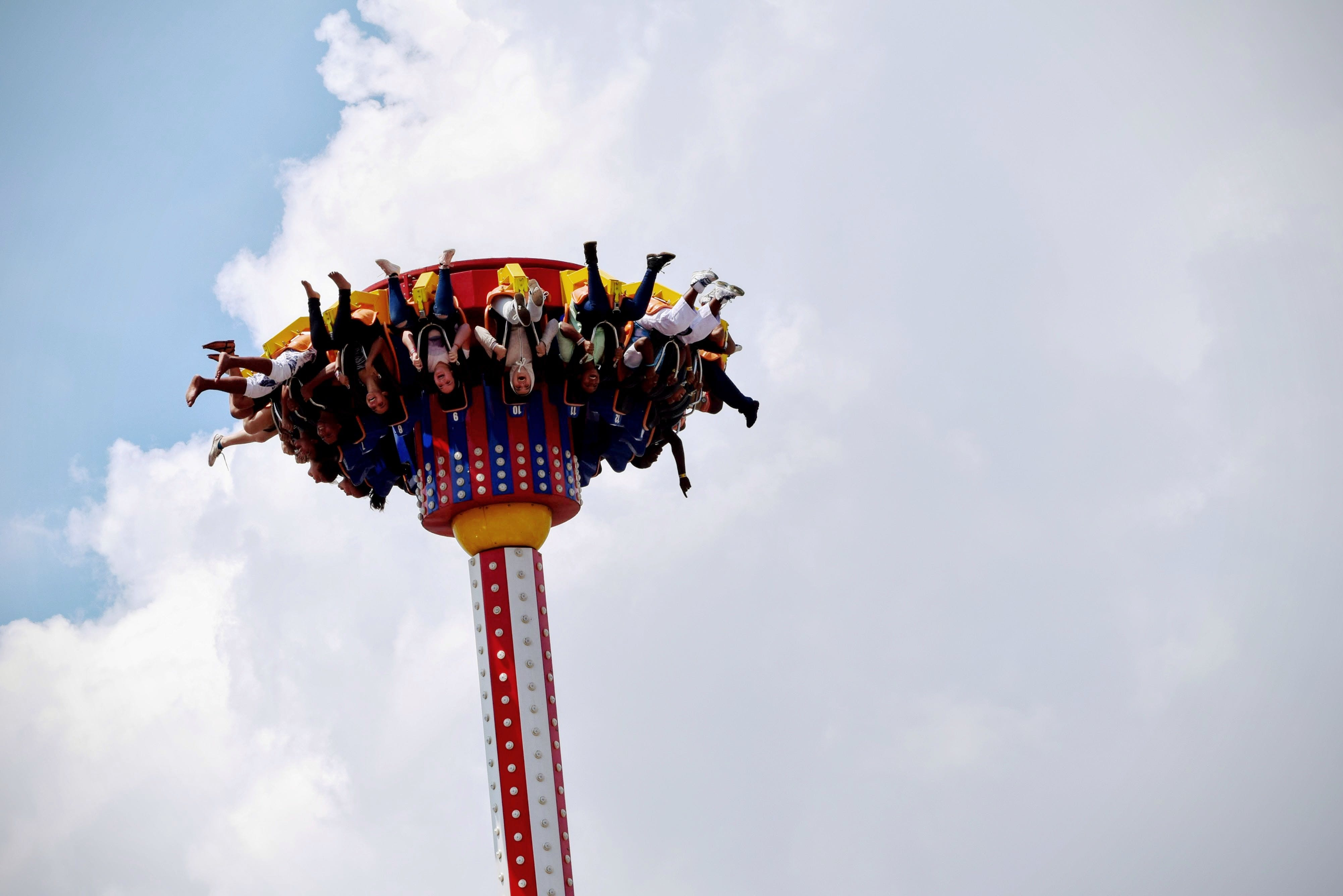 People Riding on White and Red Carnival Rides