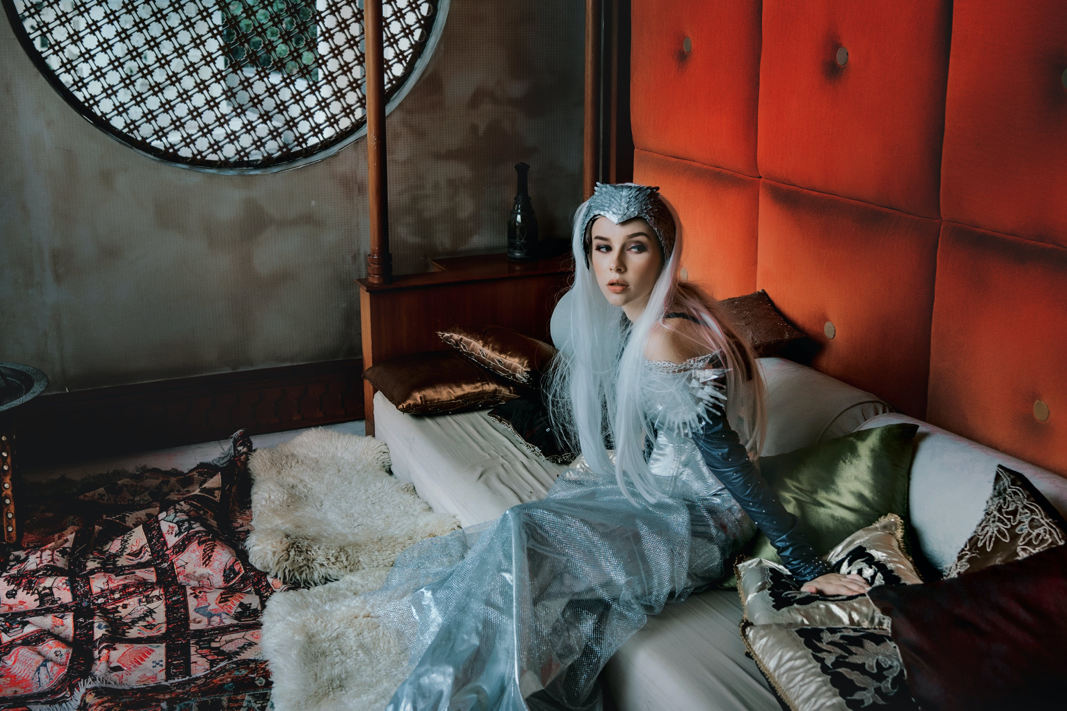 Woman in Silver Dress Sitting on Bed