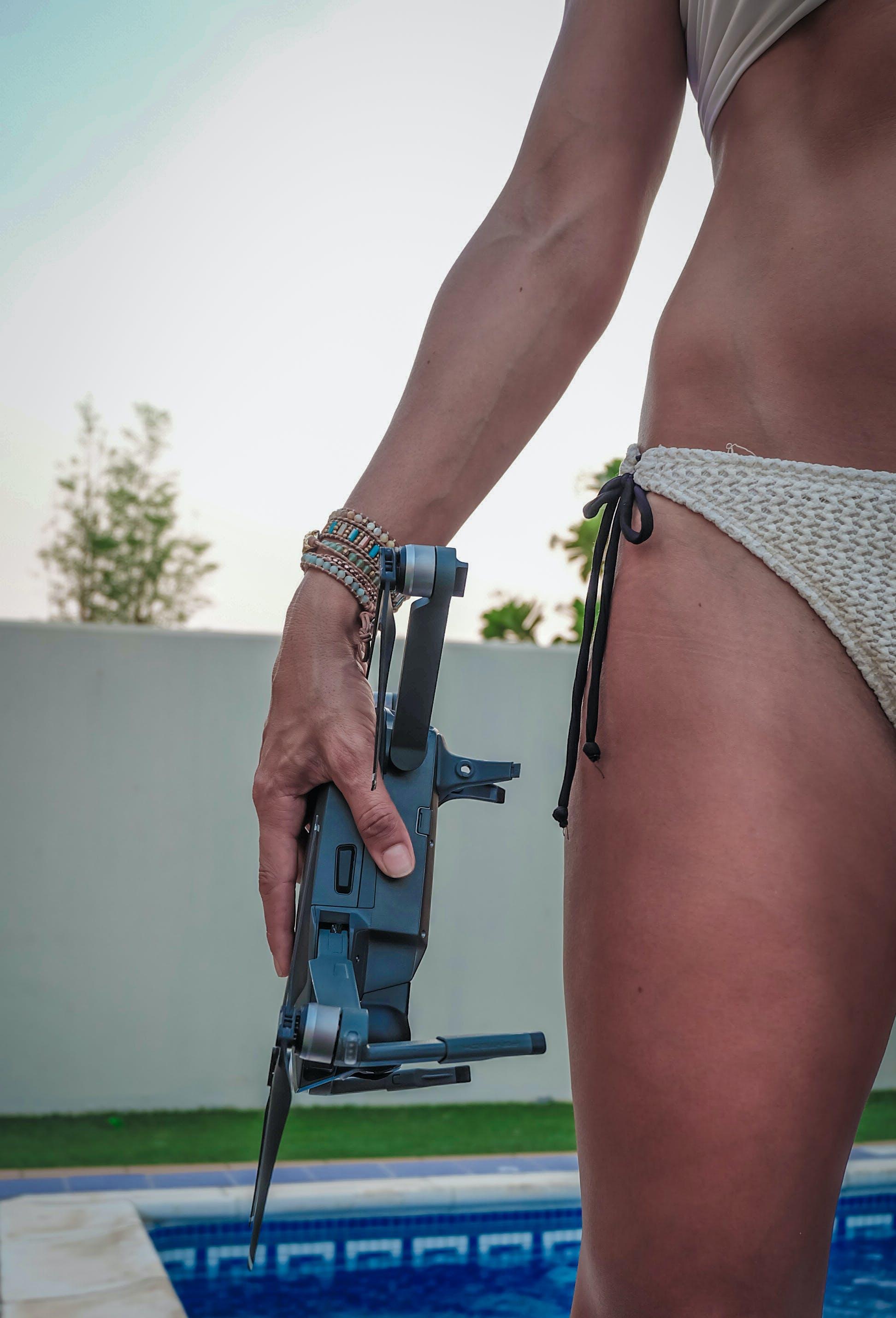 Woman in Gray Bikini Holding Quadcopter on Swimming Pool