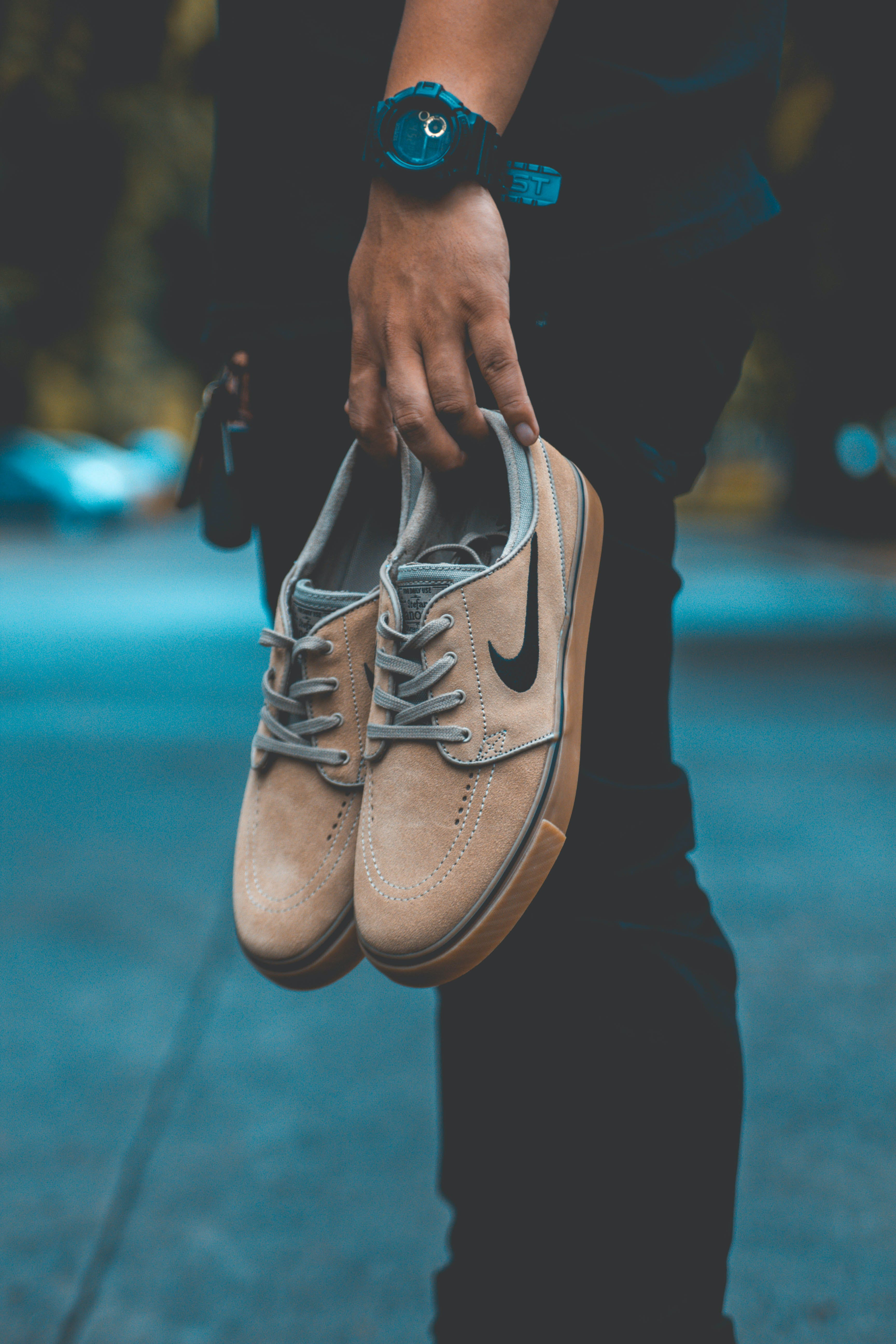 Person Holding Pair of Brown Nike Sneakers