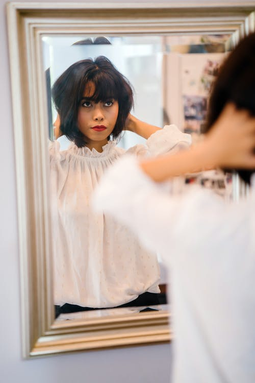 Selective Focus Photography of Woman in Front of Mirror