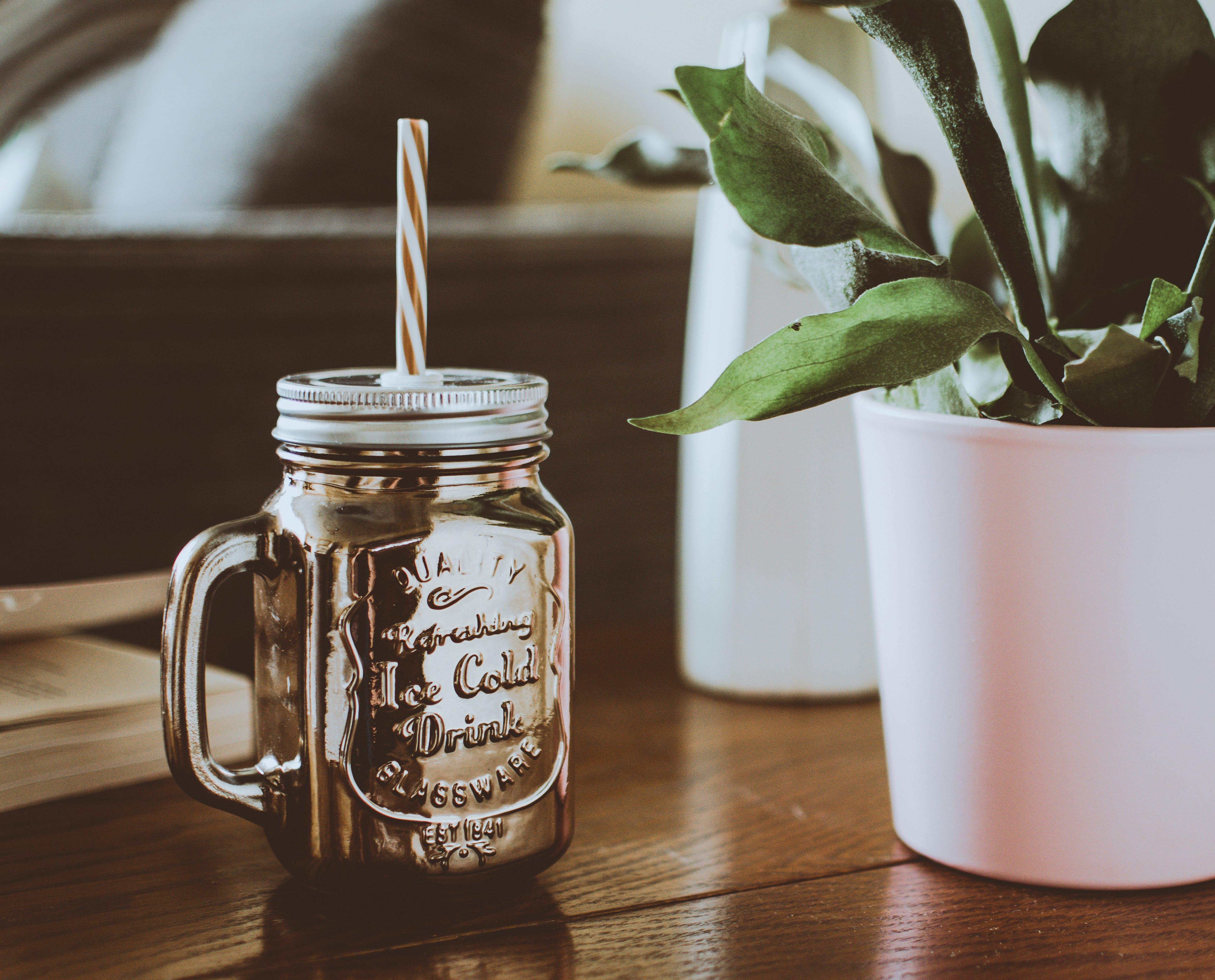 Brown Mason Jar Mug With Straw Beside Plant on Table