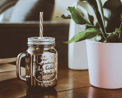Brown Mason Jar Mug With Straw Beside Plant on Table