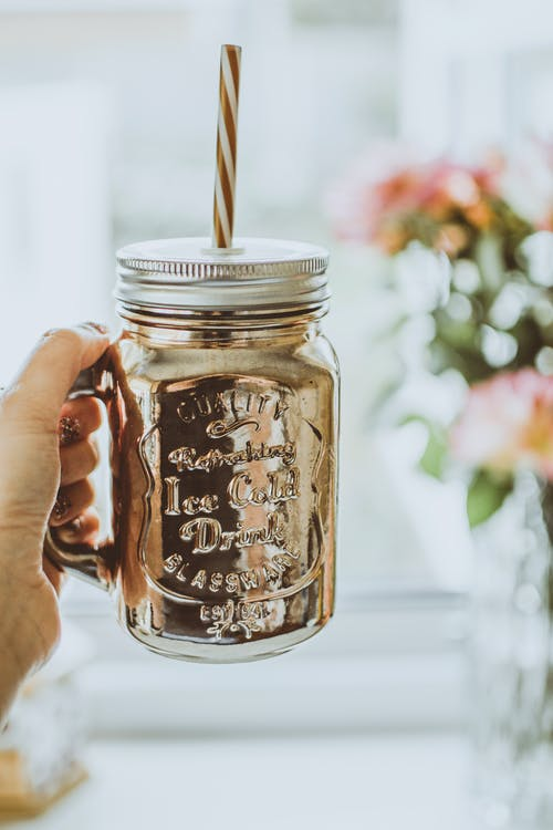 Person Holding Brown Mason Jar Mug