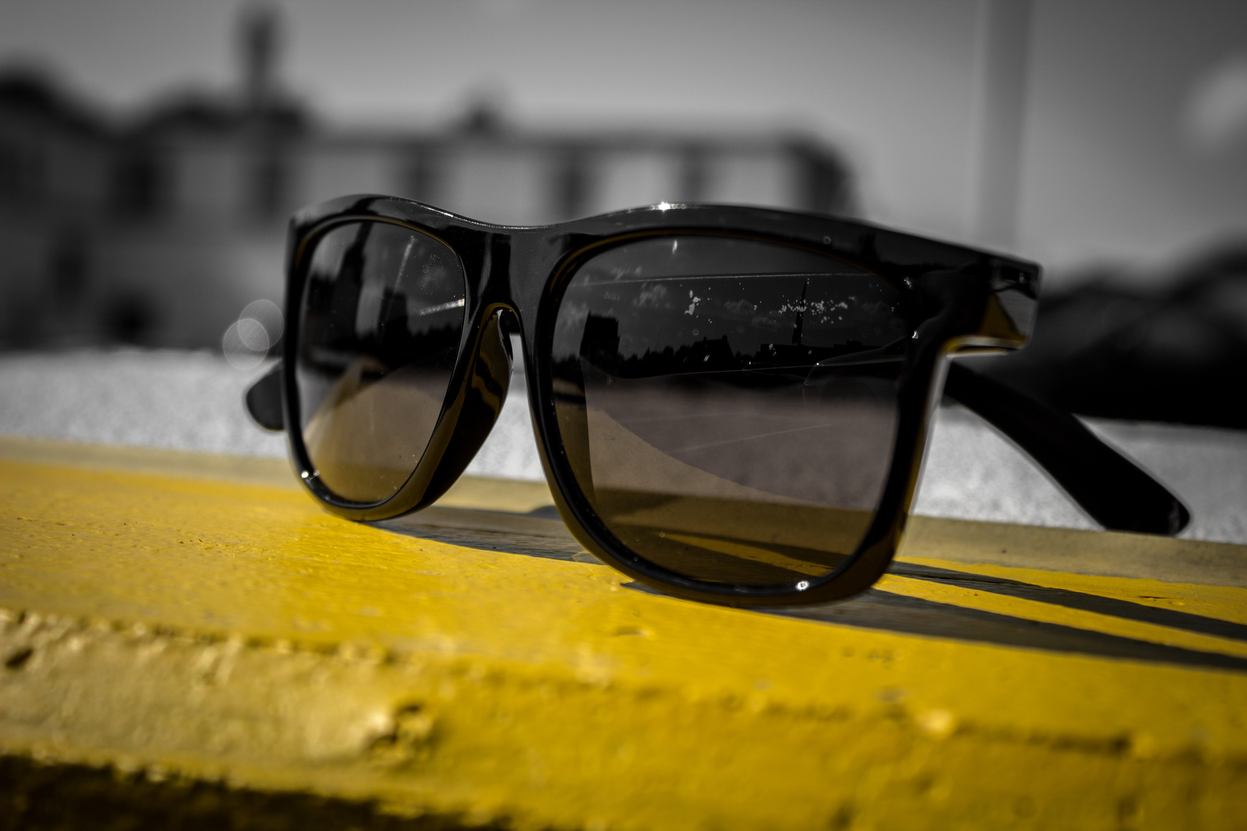 Black Sunglasses on Yellow Wooden Surface