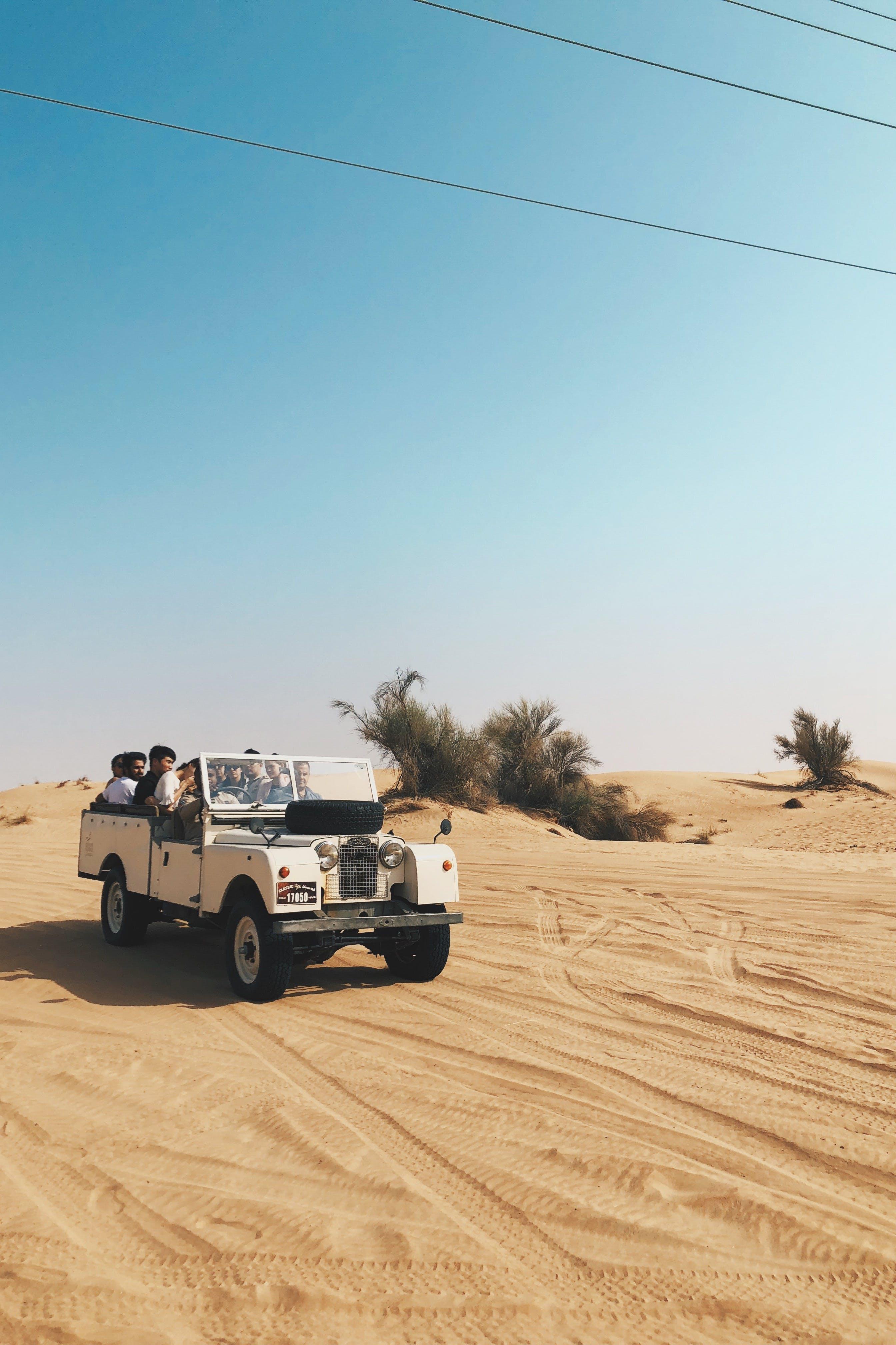 People Riding Vehicle on Desert