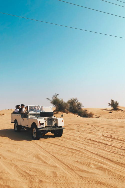 People Riding Vehicle on Desert
