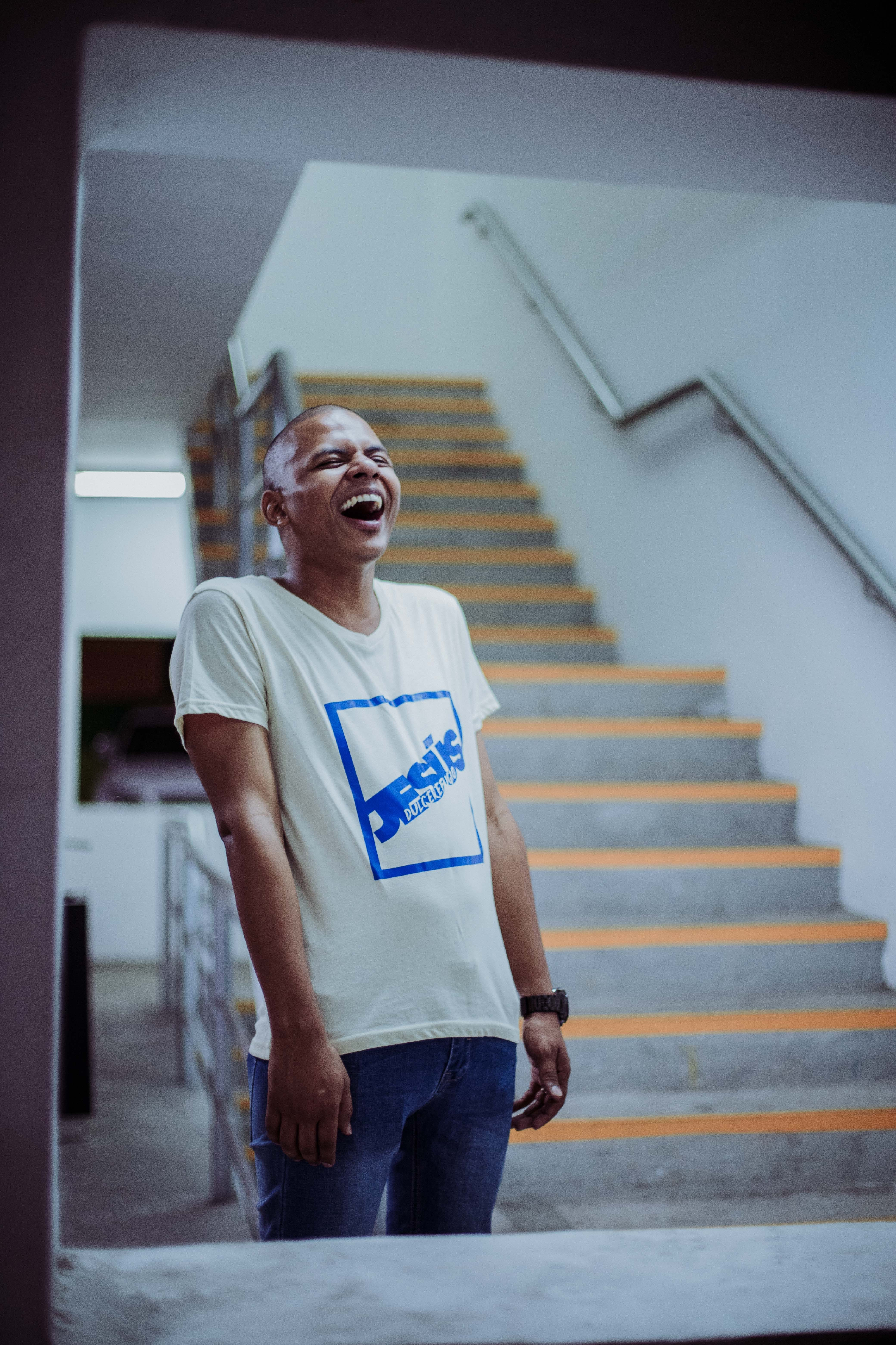 Photo of Man Standing Near Stairs Laughing