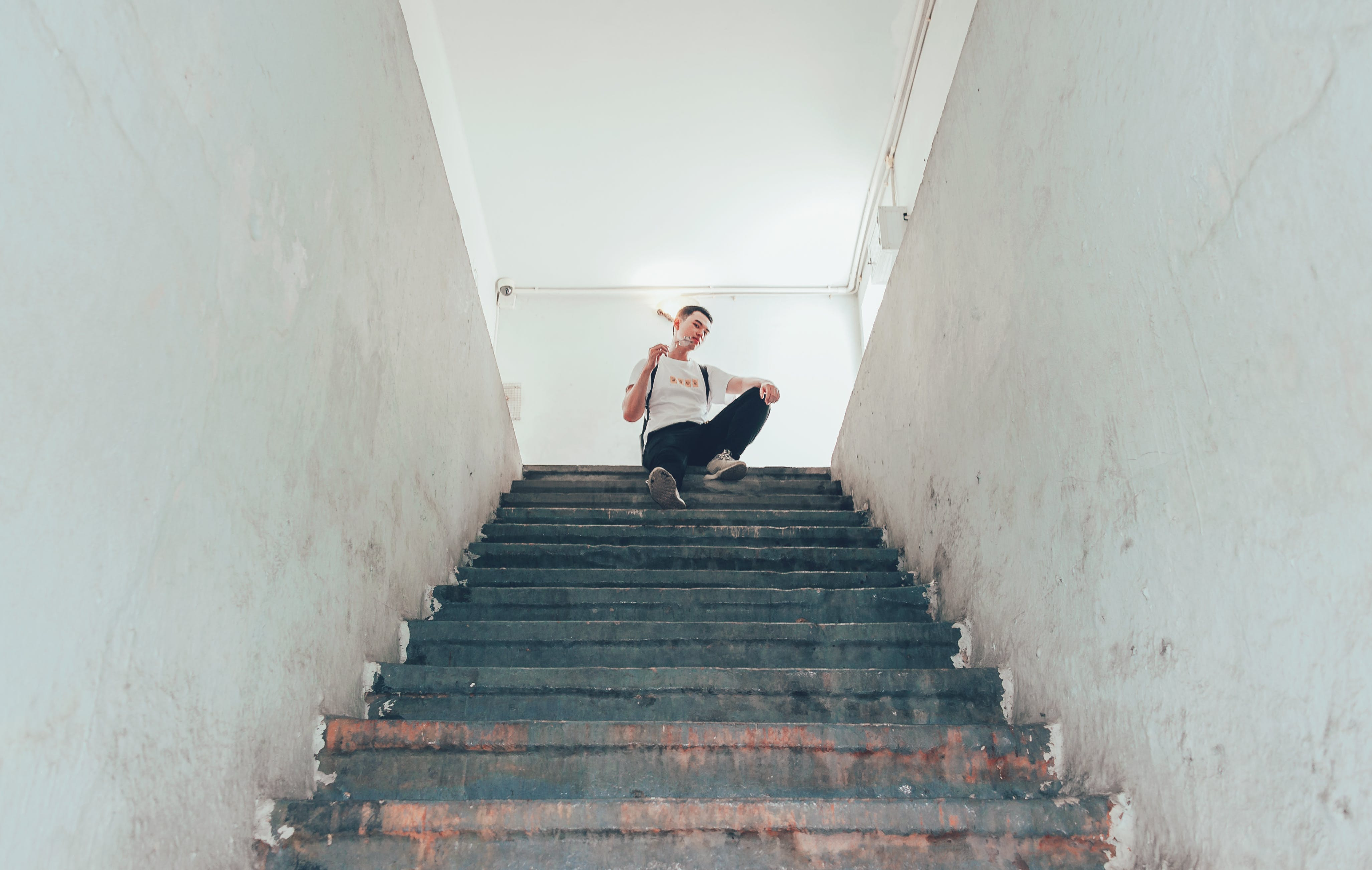 Man In White Top Sitting On Top Of Stairs