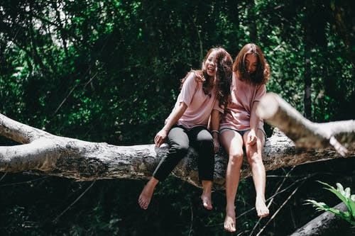 Two Woman Sitting on Tree Log
