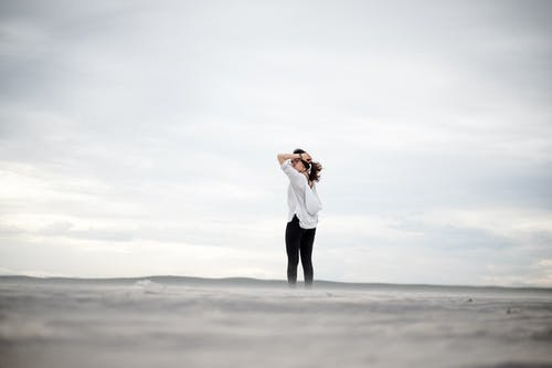 Woman Standing Alone While Holding Her Hair
