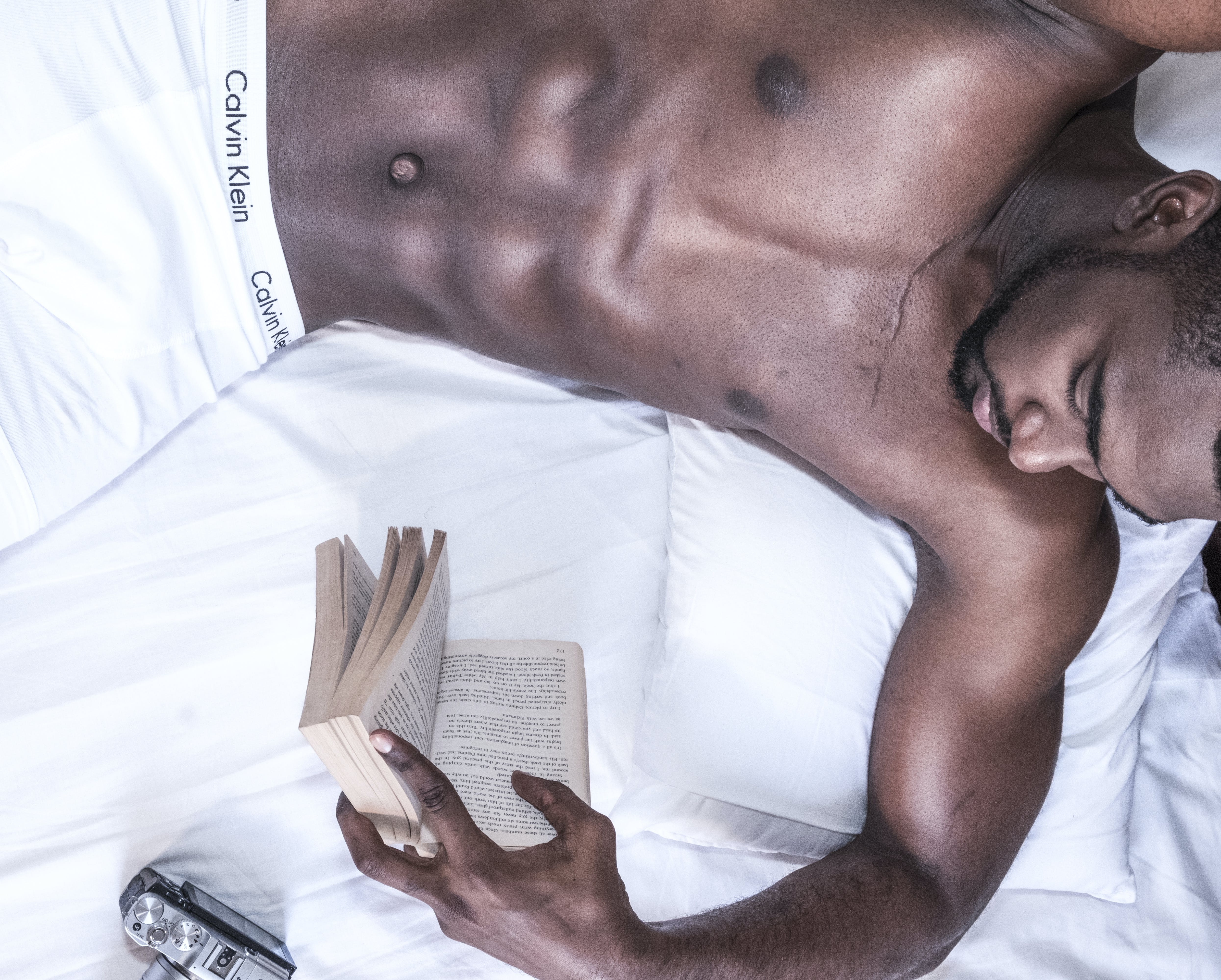 Man Holding Book Lying On Bed