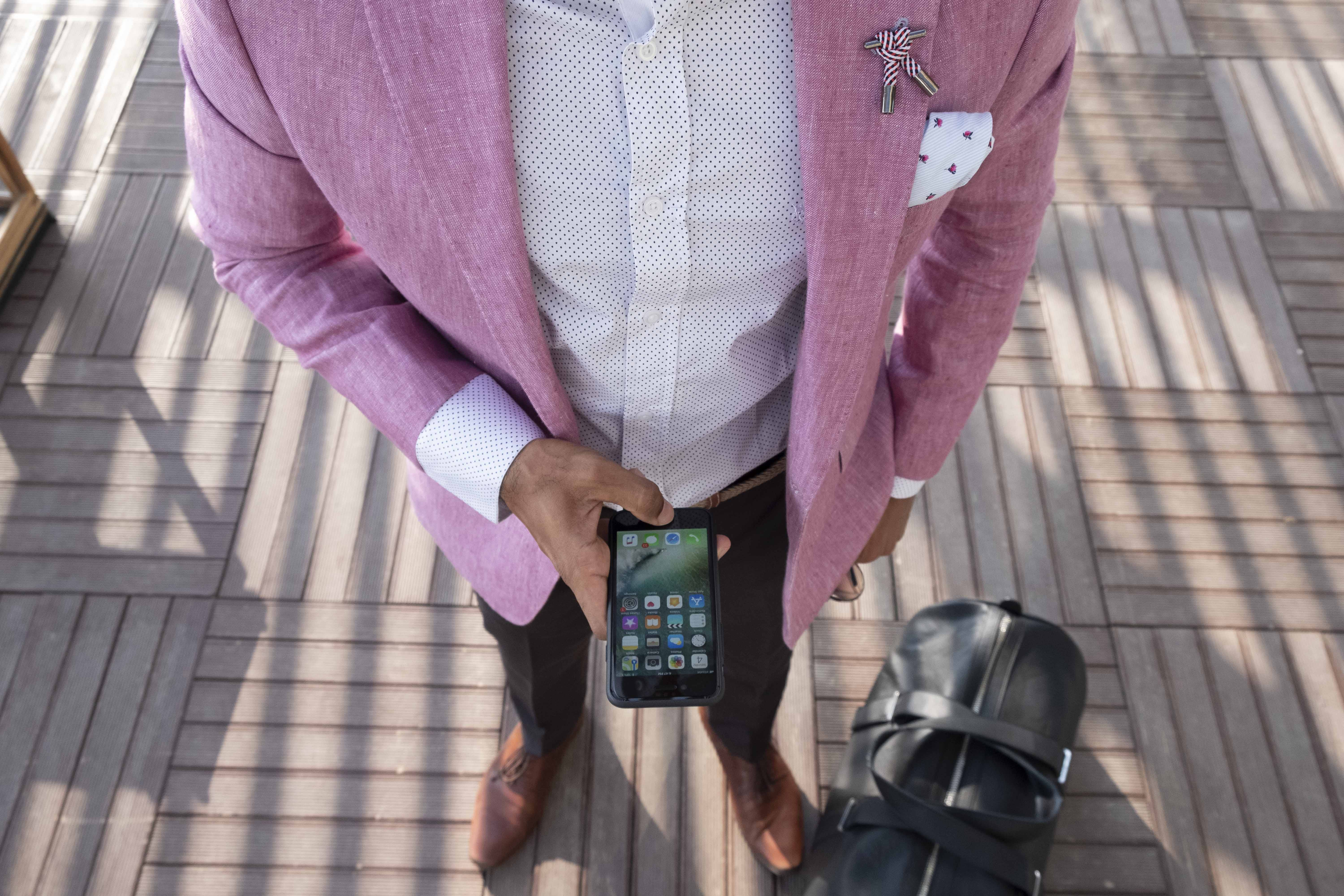 Person Standing Beside Duffel Bag While Using Smartphone