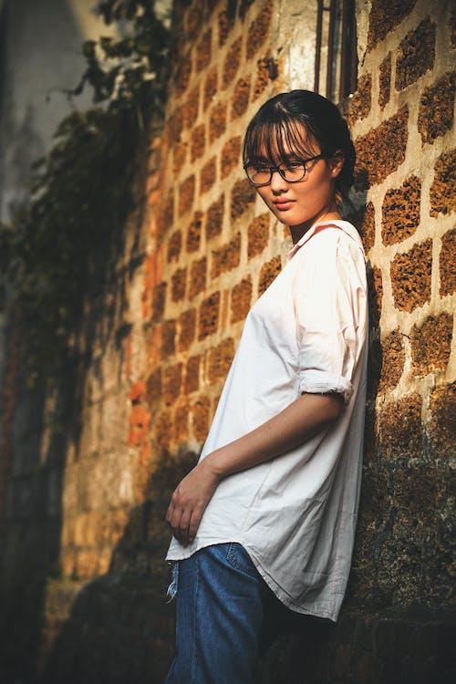 斜倚在棕色磚牆上的女人