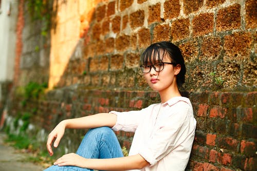 Woman Leaning on Bricked Wall
