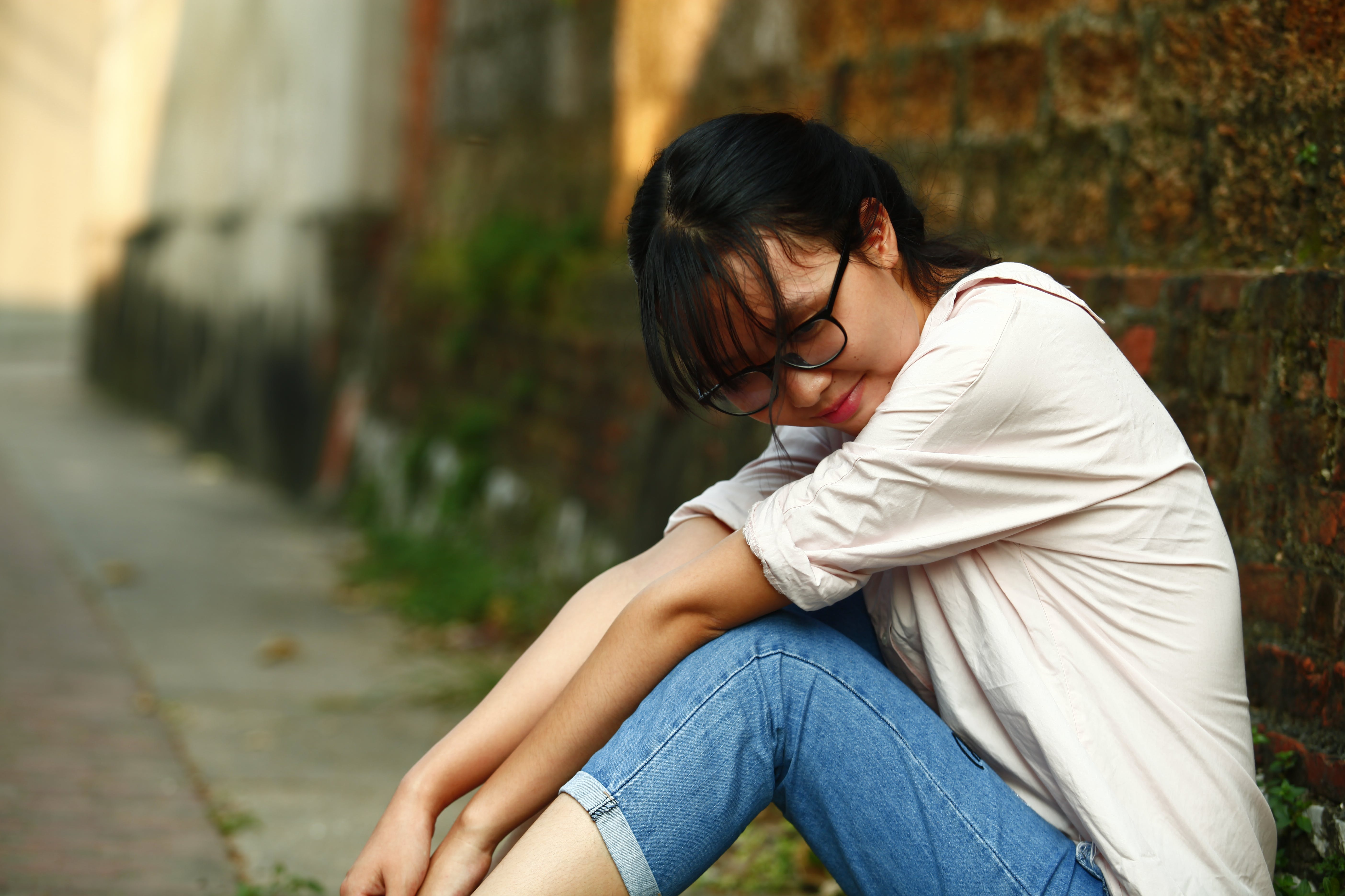 Smiling Woman Sitting Beside Bricked Brown Wall