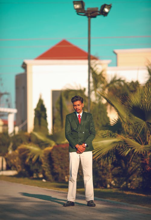 Man Standing on Road Near Bushes