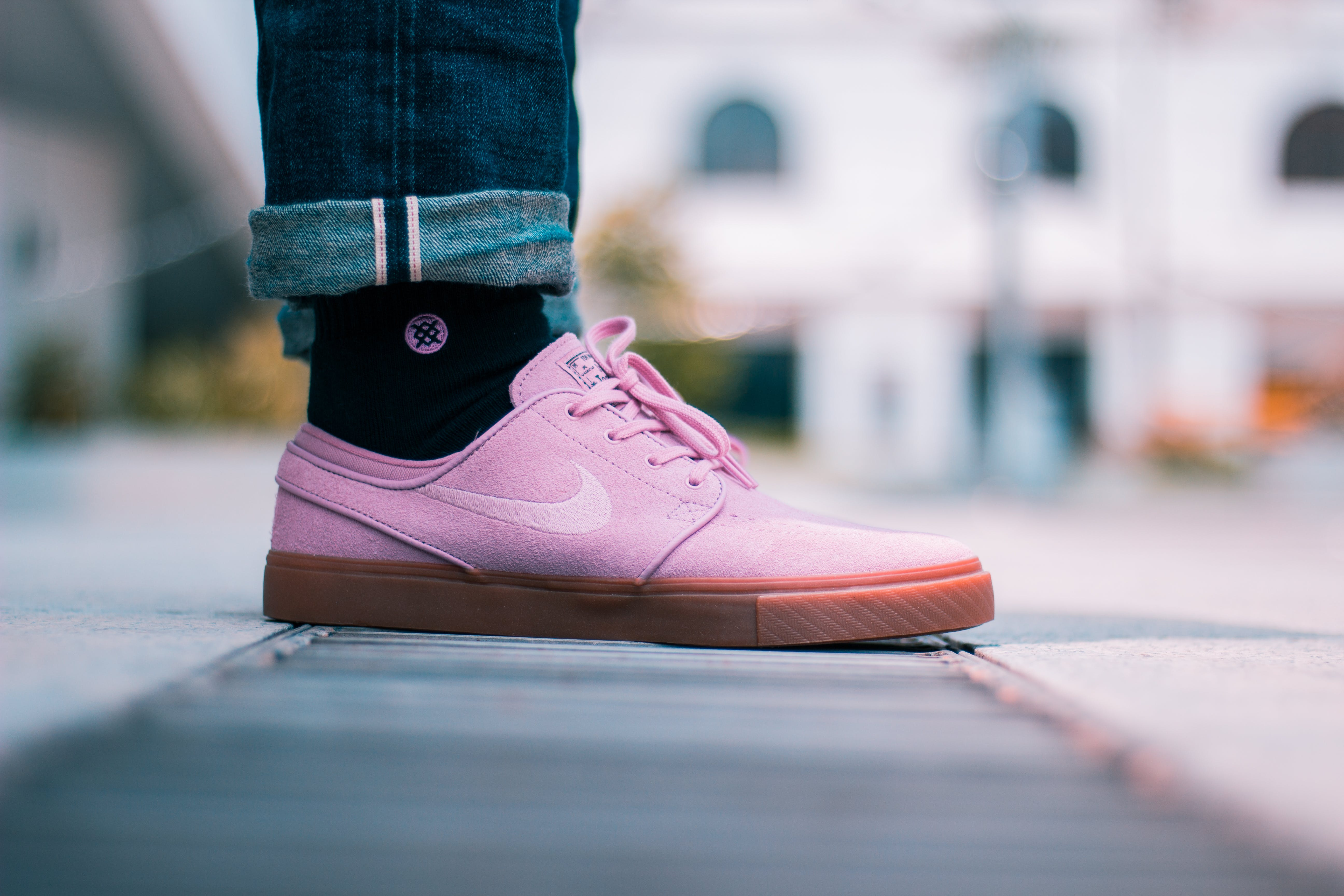 Selective Focus Photo of Person Wearing Pink Nike Low-top Sneakers