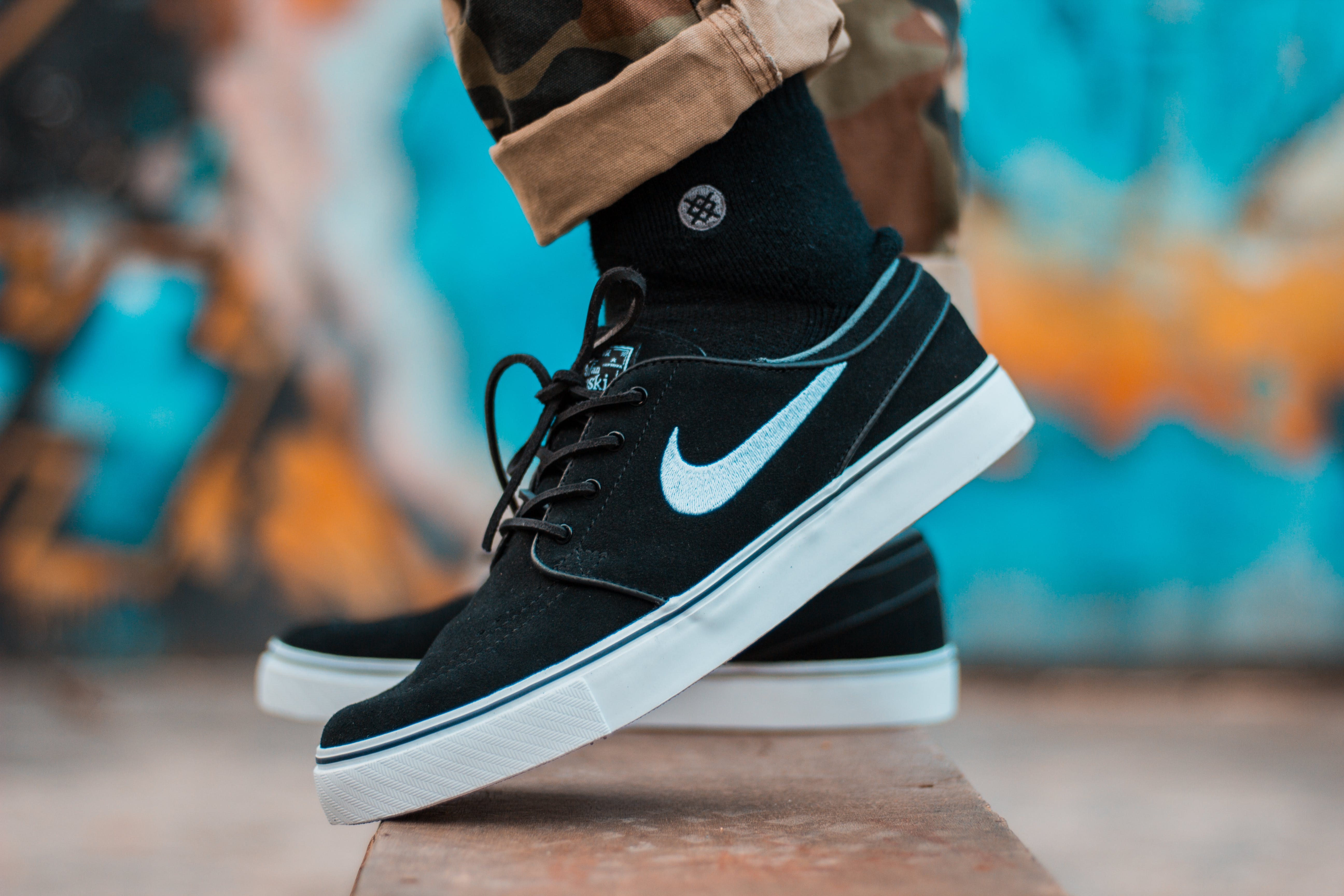 Person in Brown Camouflage Pants and Black Nike Sb Stefan Janoski With Black Socks