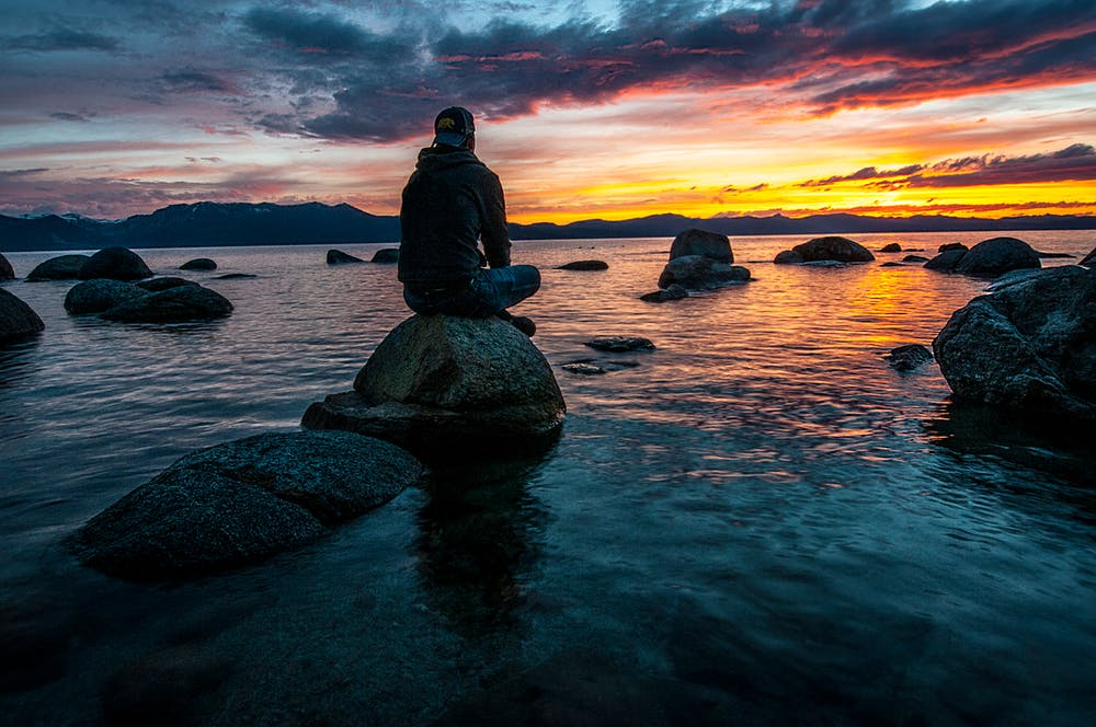 Man sitting on rock | Photo: Pexels