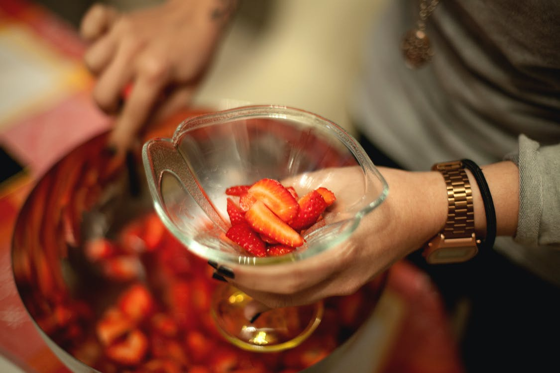Person Holding Goblet Glass With Slice Strawberries