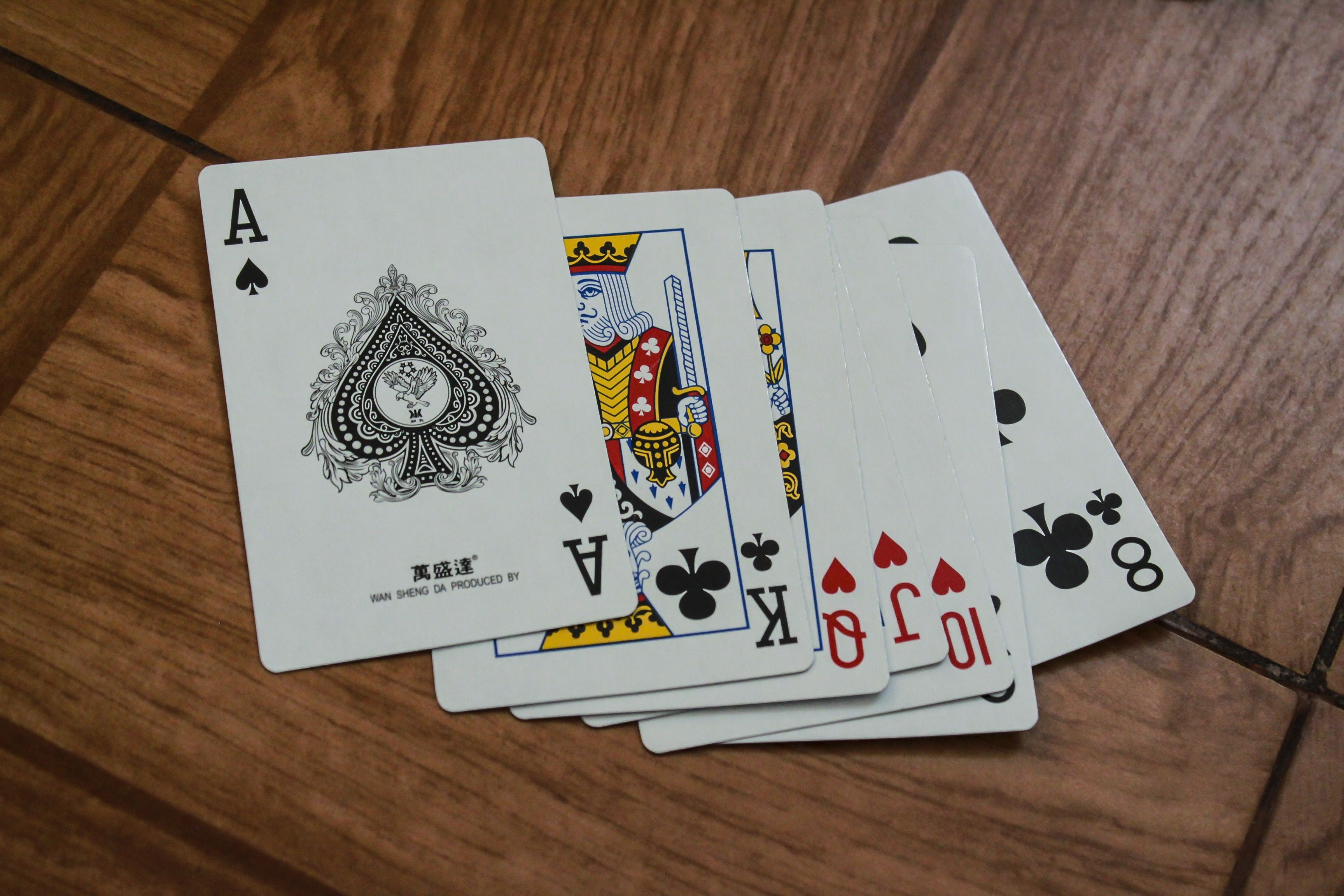 Seven Assorted Playing Cards on Brown Wooden Surface