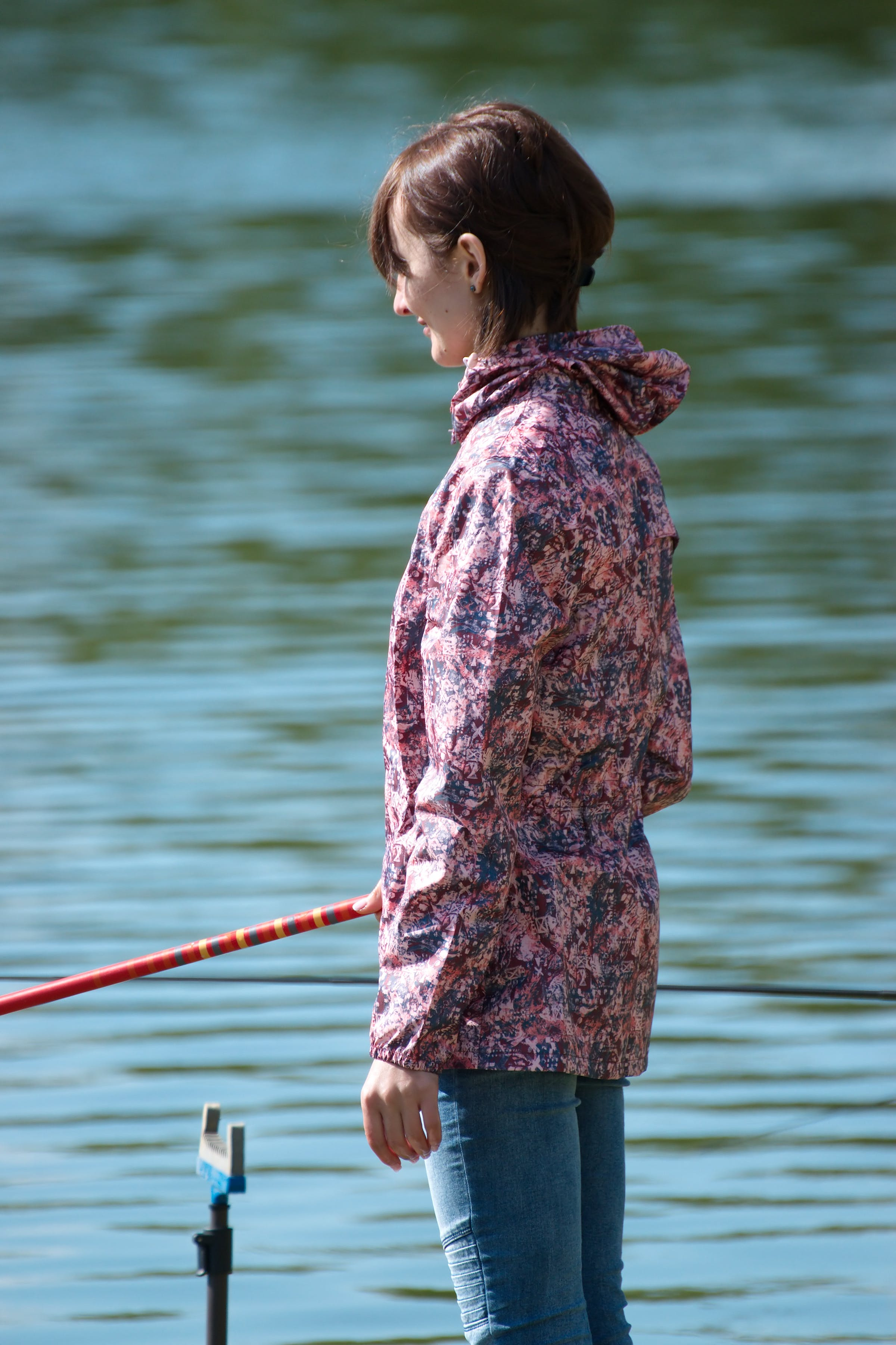 Selective Focus Photography of Woman Holding Red Fishing Rod Standing Beside Calm Body of Water