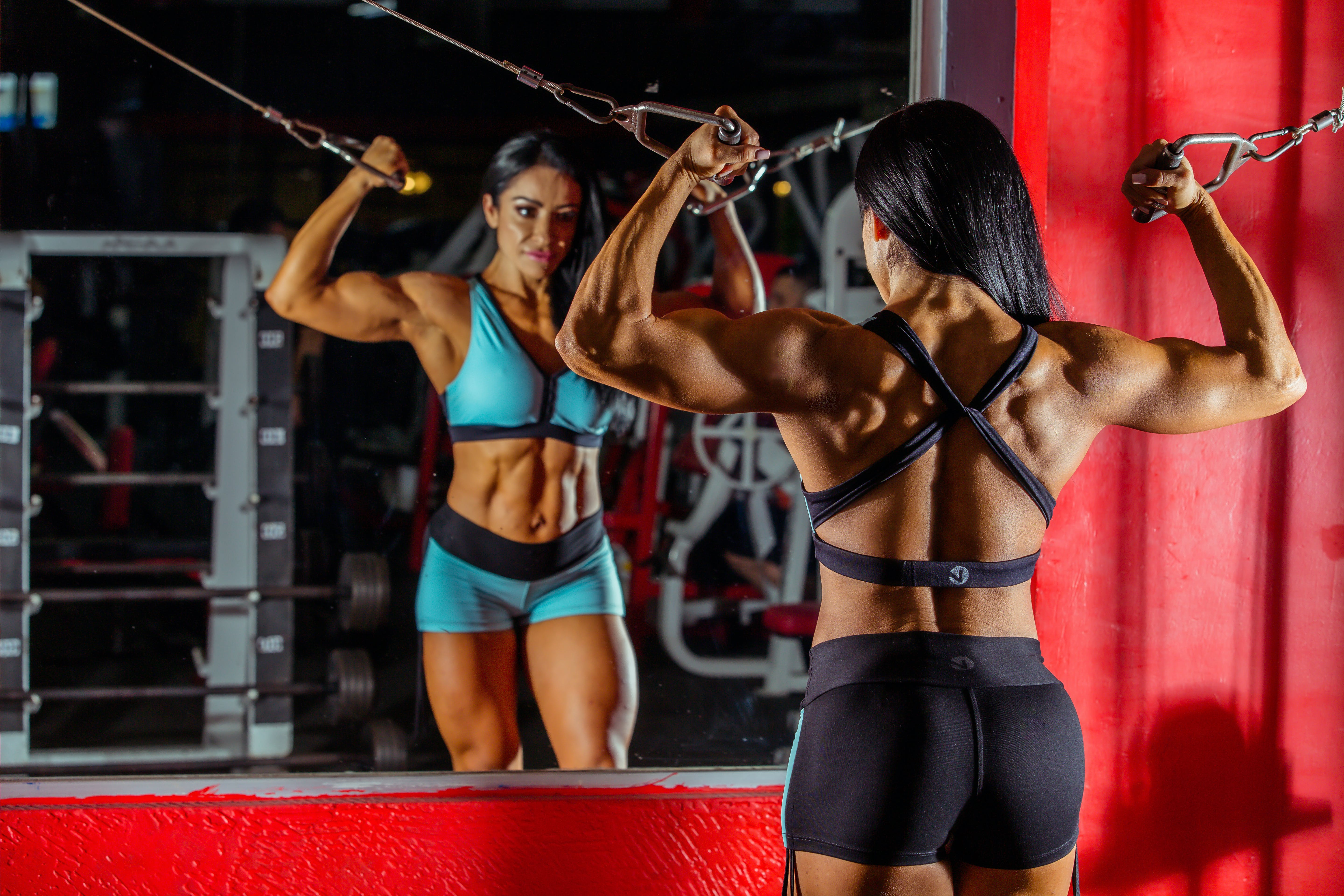 Photo Woman Bodybuilder Using Cable and Pulley Machine While Facing Mirror