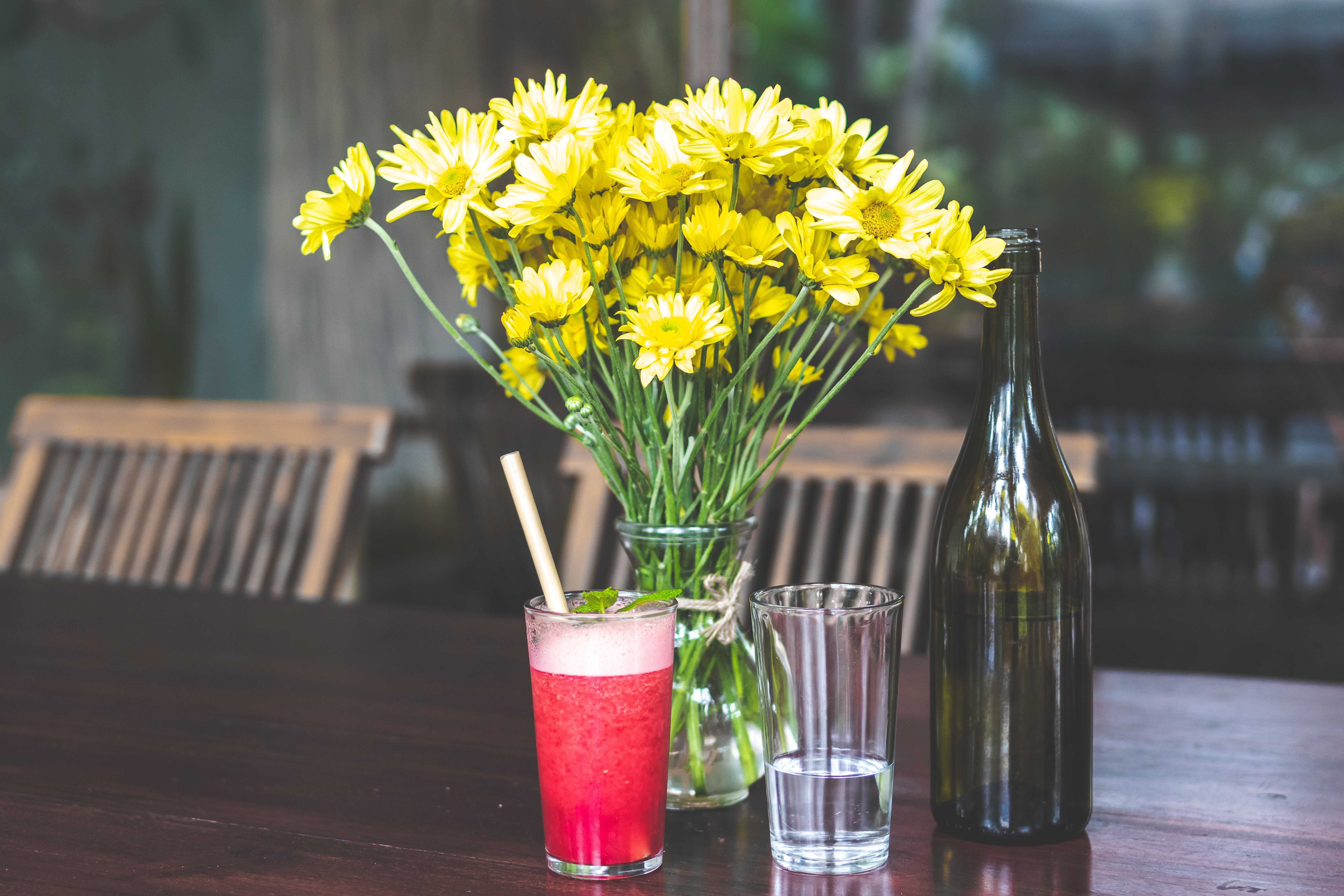 Yellow Daises in Clear Glass Vase Beside Bottle