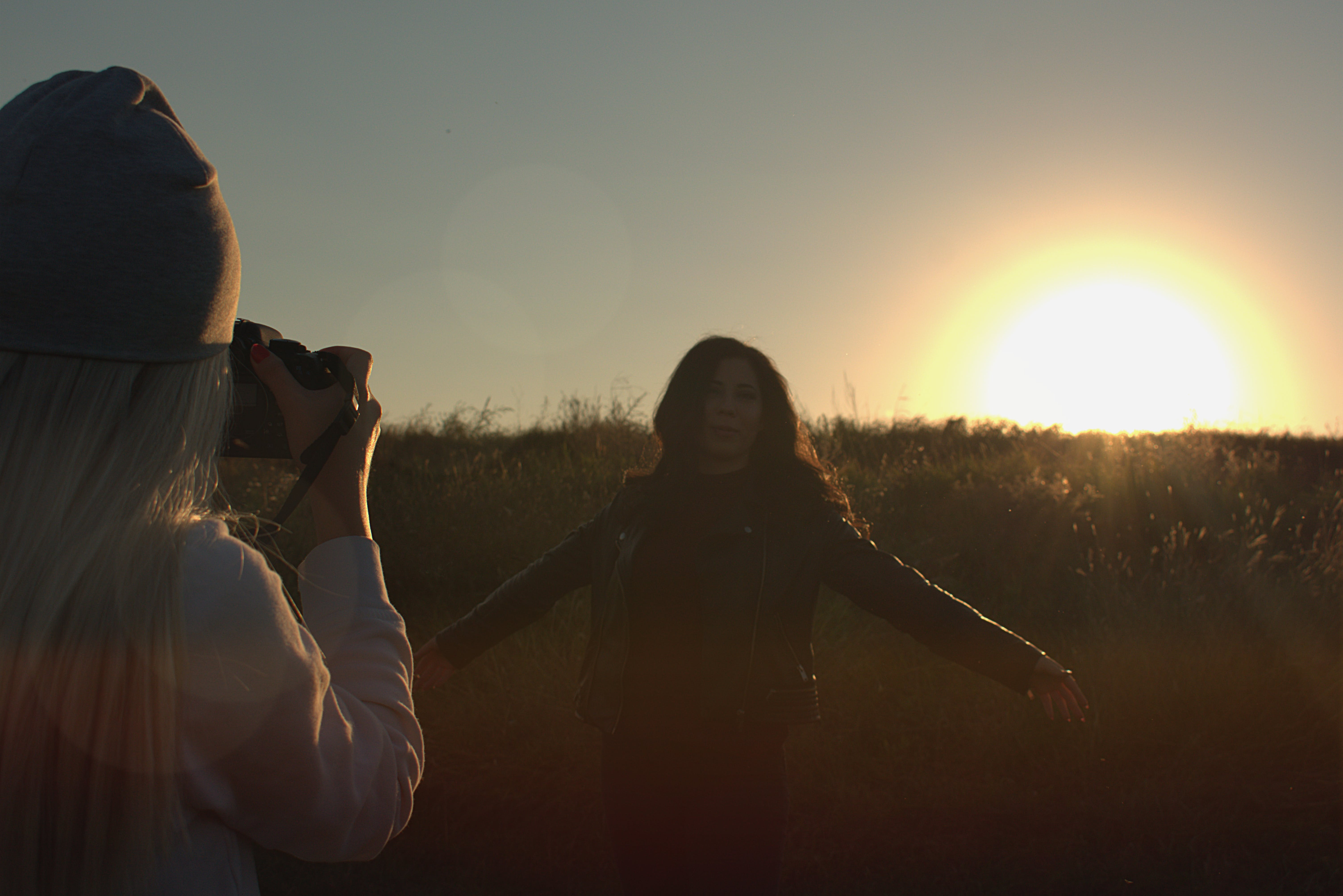 Person Taking Photo of Another Person during Sunset