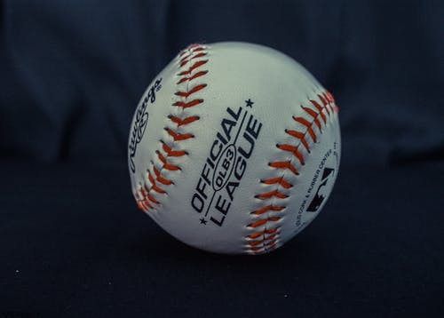 White and Orange Official League Baseball on Black Textile