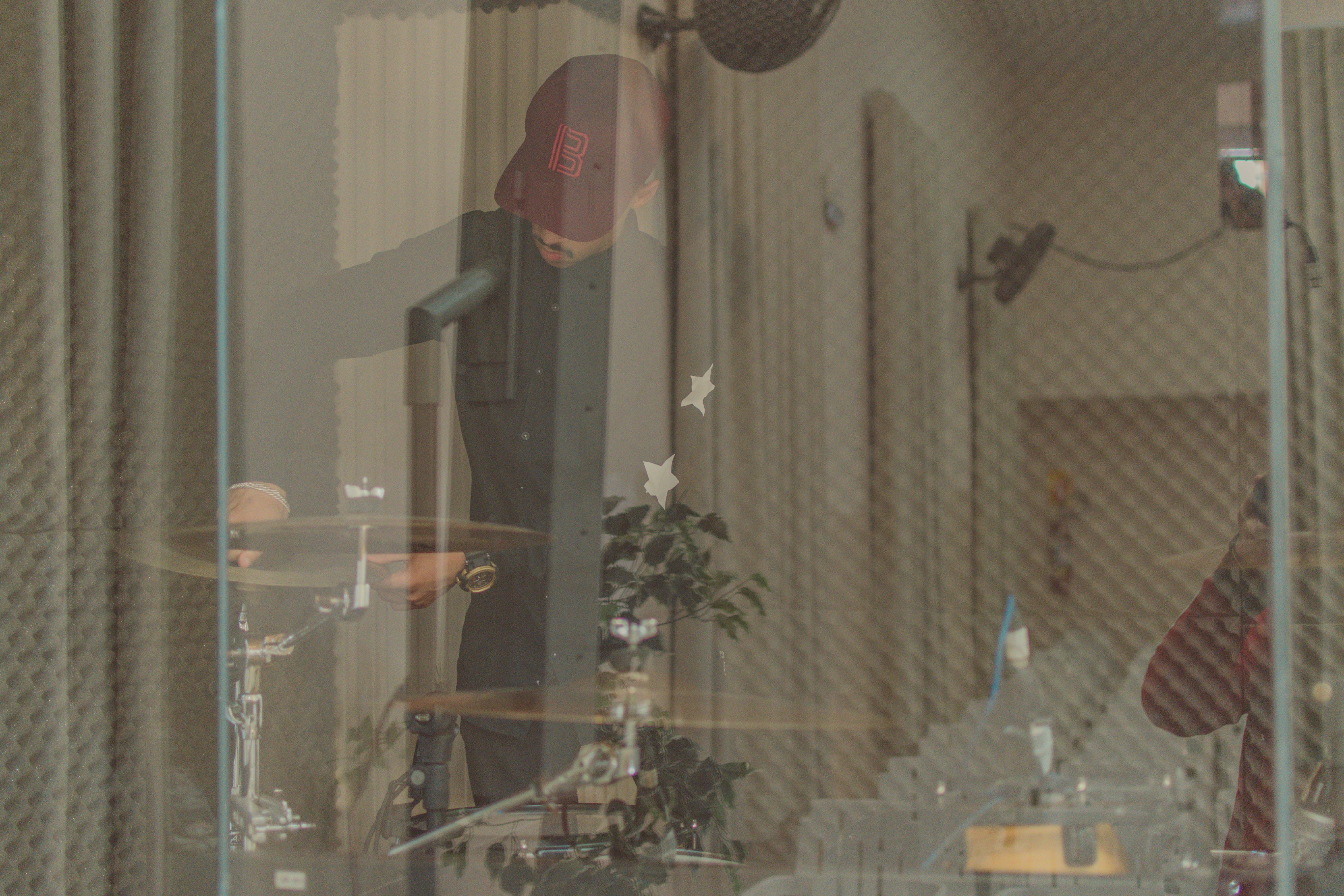 Man Standing Front of Drum in Room