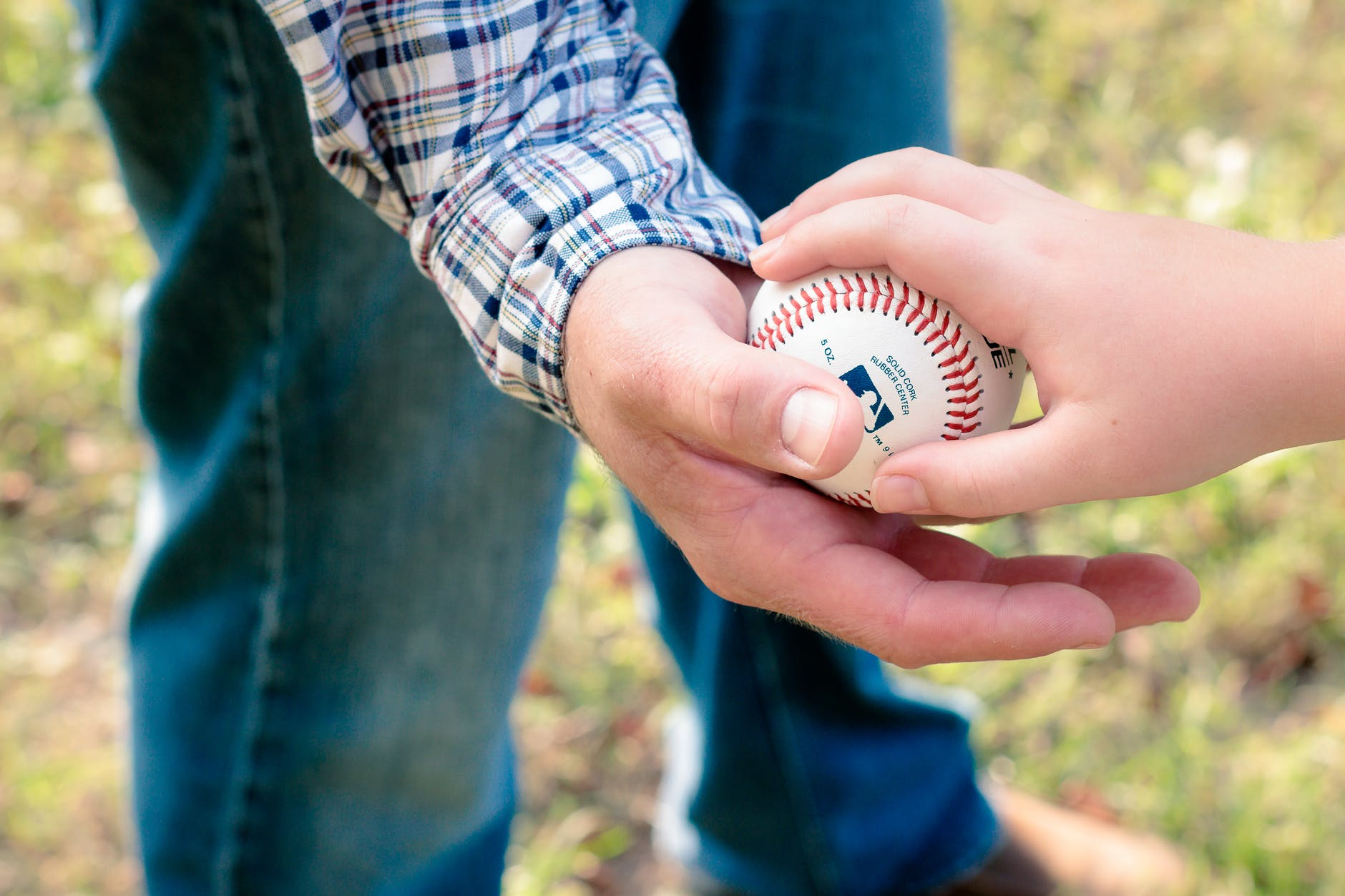 Two person holding a baseball