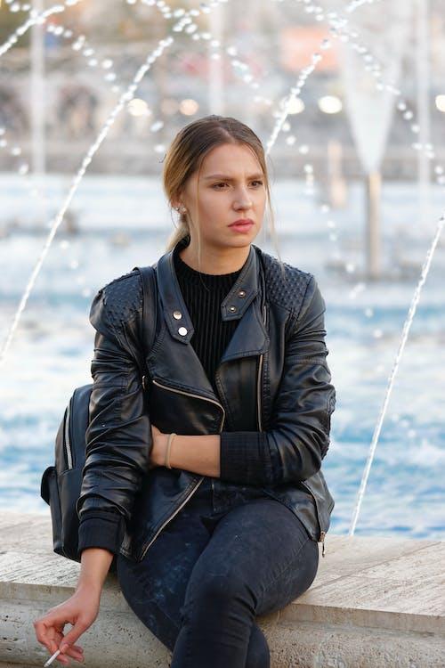 Woman Sitting Beside Fountain