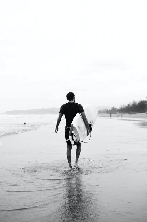 Grayscale Photo of Man Carrying Surfboard