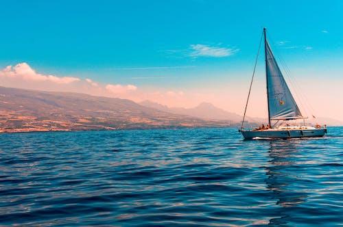 Foto profissional grátis de água, barco a vela, céu azul, céu de brigadeiro