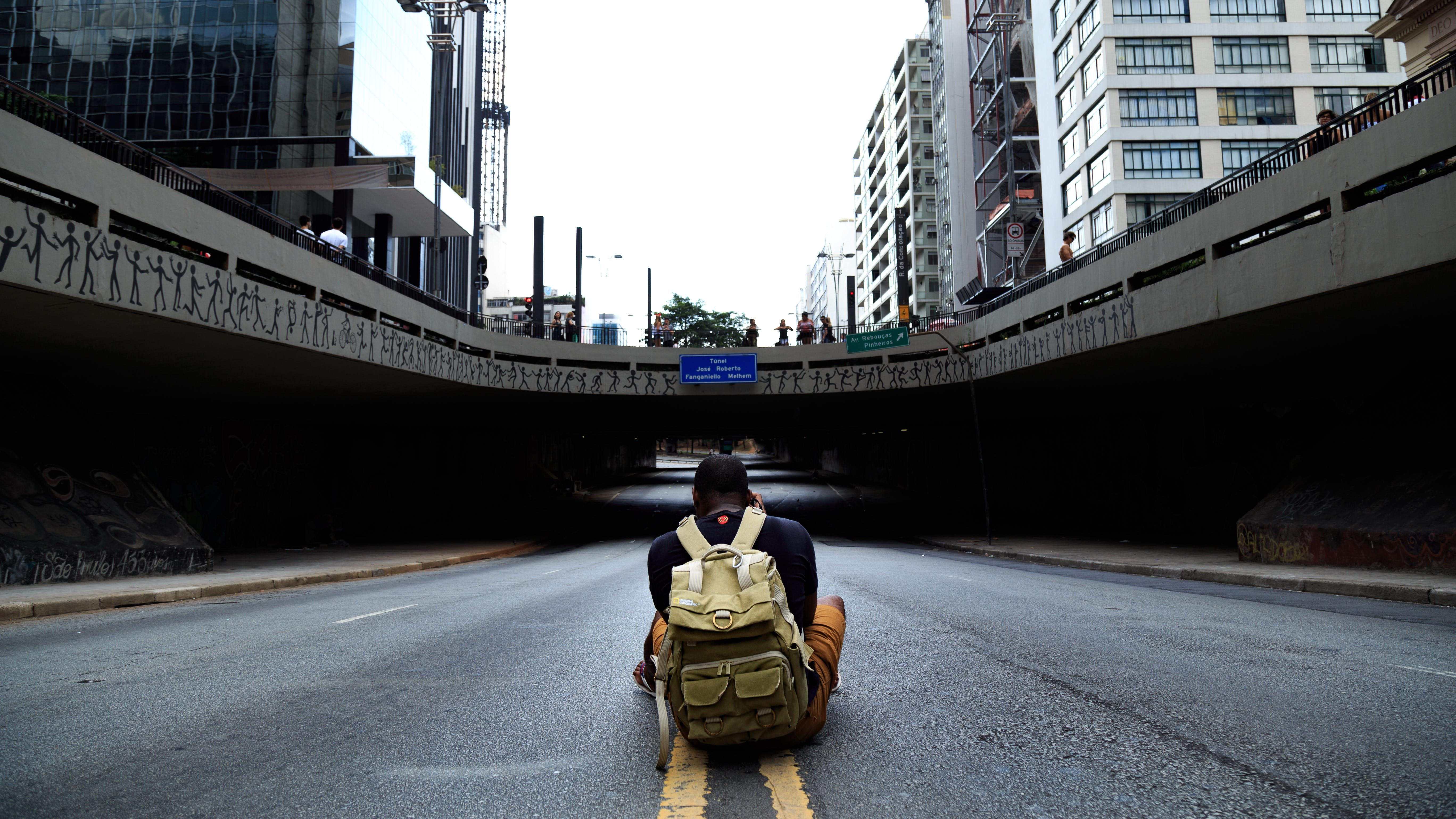 Photo of Man Sitting in Middle of Road