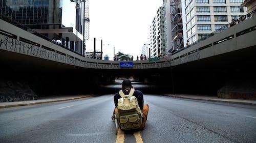 Foto Des Mannes, Der In Der Mitte Der Straße Sitzt