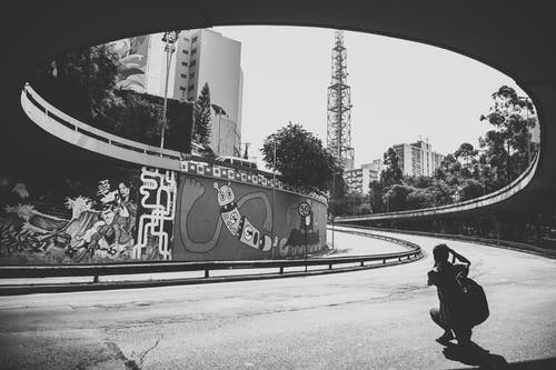 Man Taking Picture of Graffiti Wall