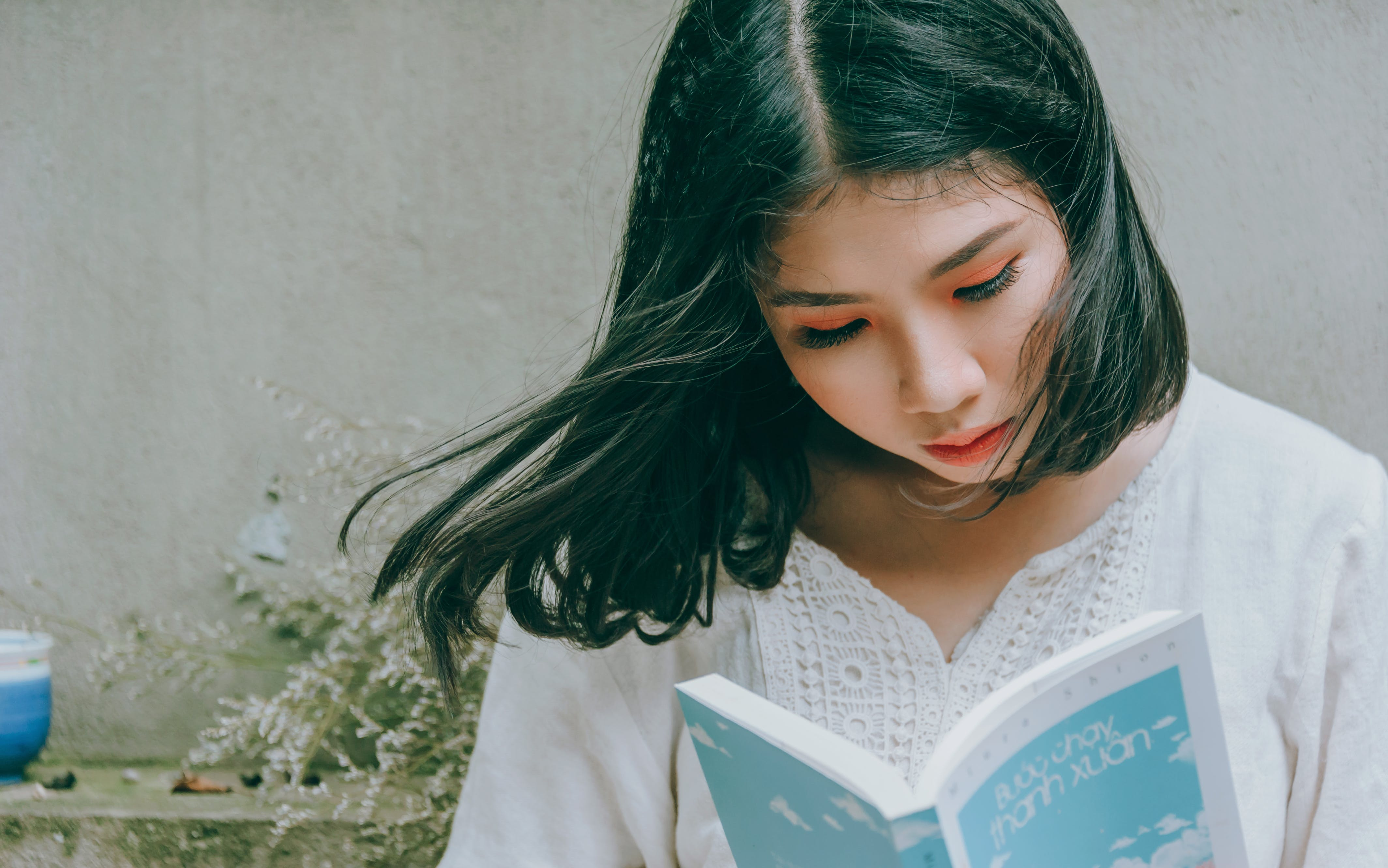 Close-Up Photo of Woman Reading Book