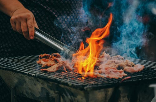 Close-Up Photo of Man Cooking Meat