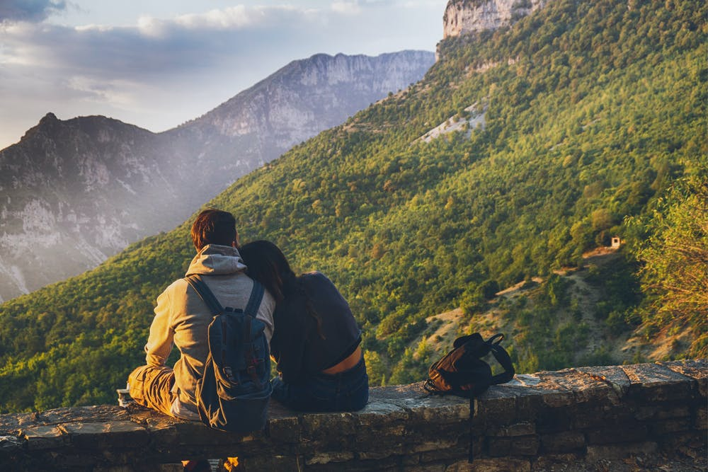 A couple sits facing the mountain.   Photo: Pexels