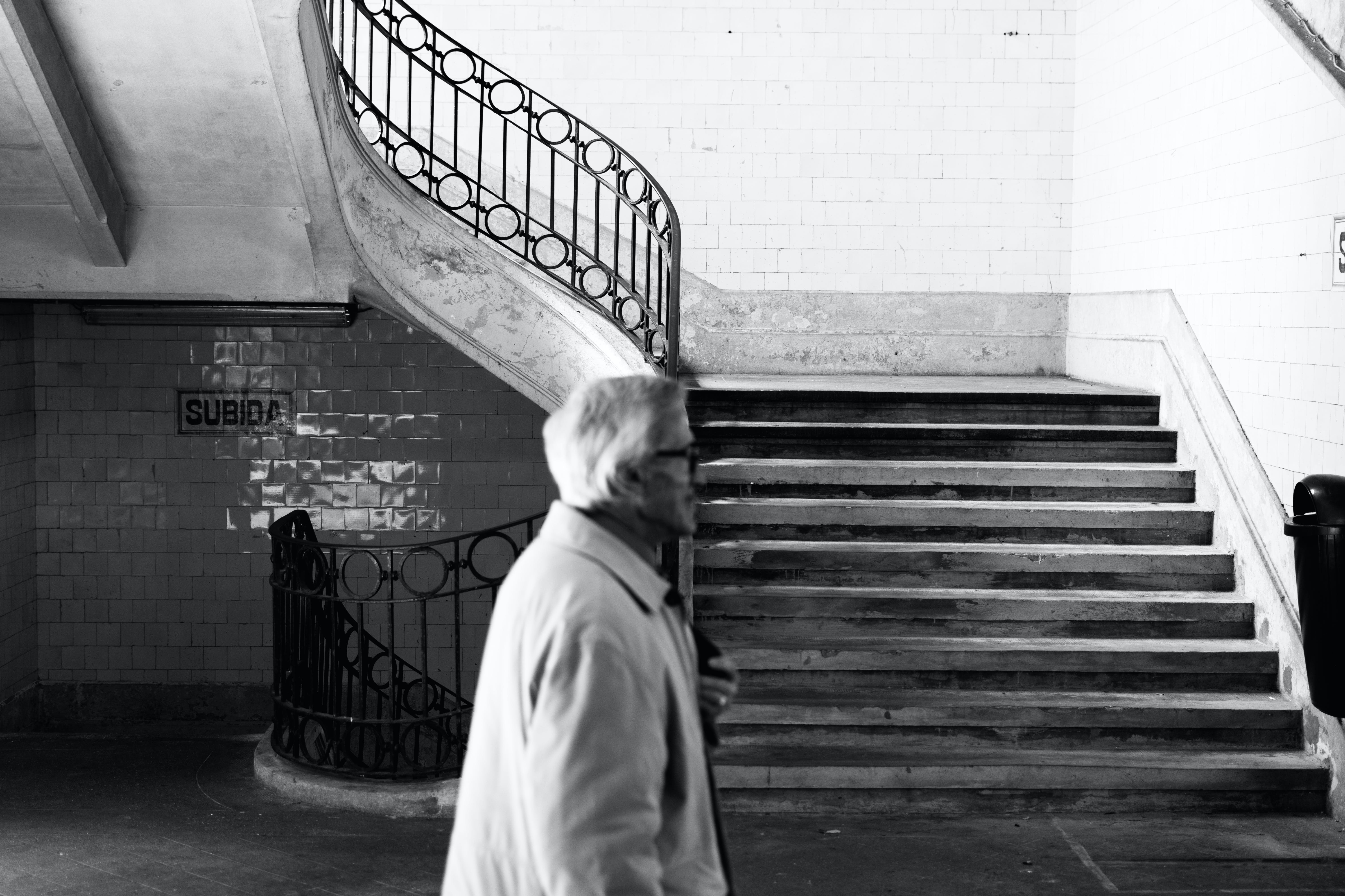 Grayscale Photography of Man Walking Near Staircase