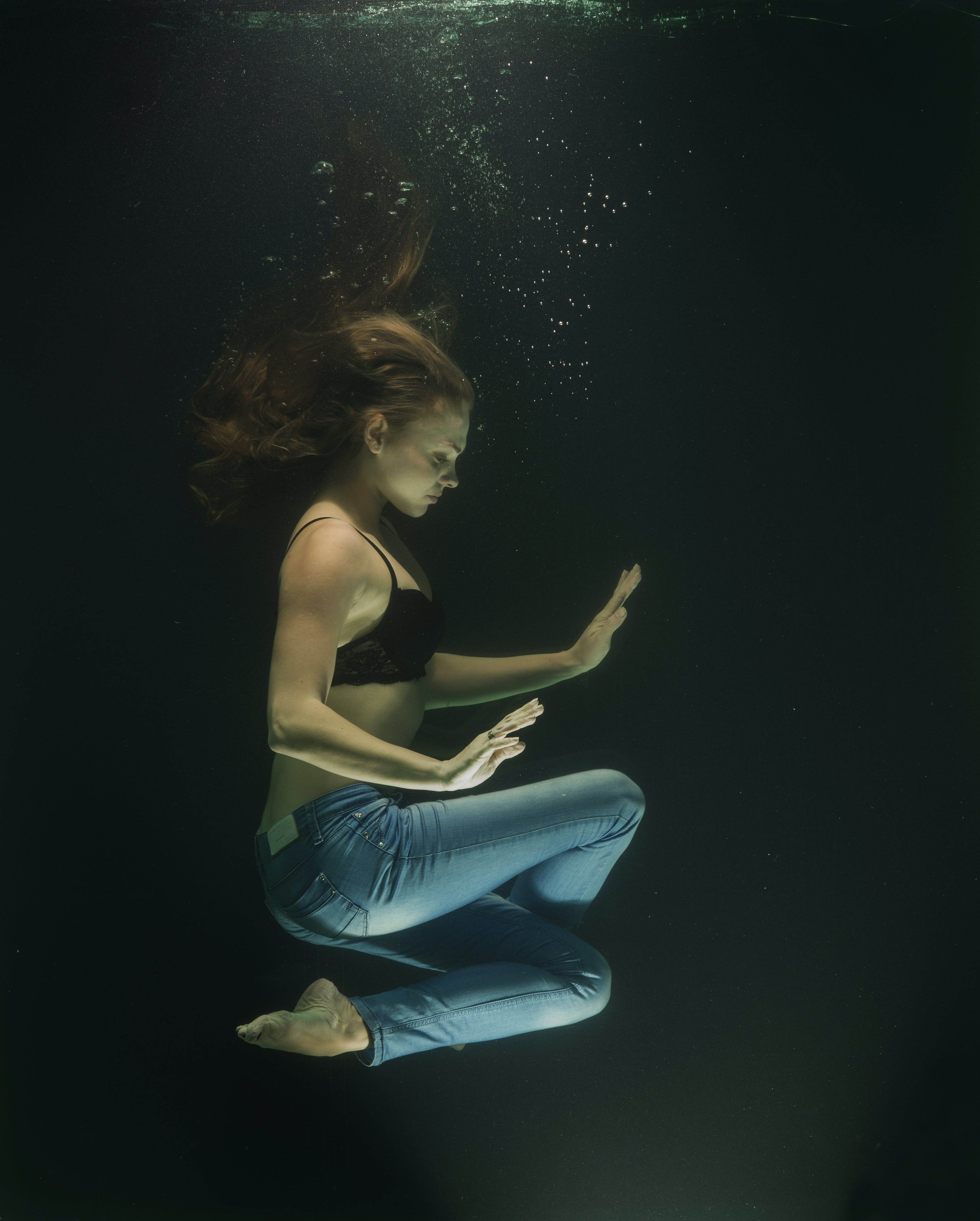 Underwater Photography of Woman Wearing Blue Jeans and Black Bra