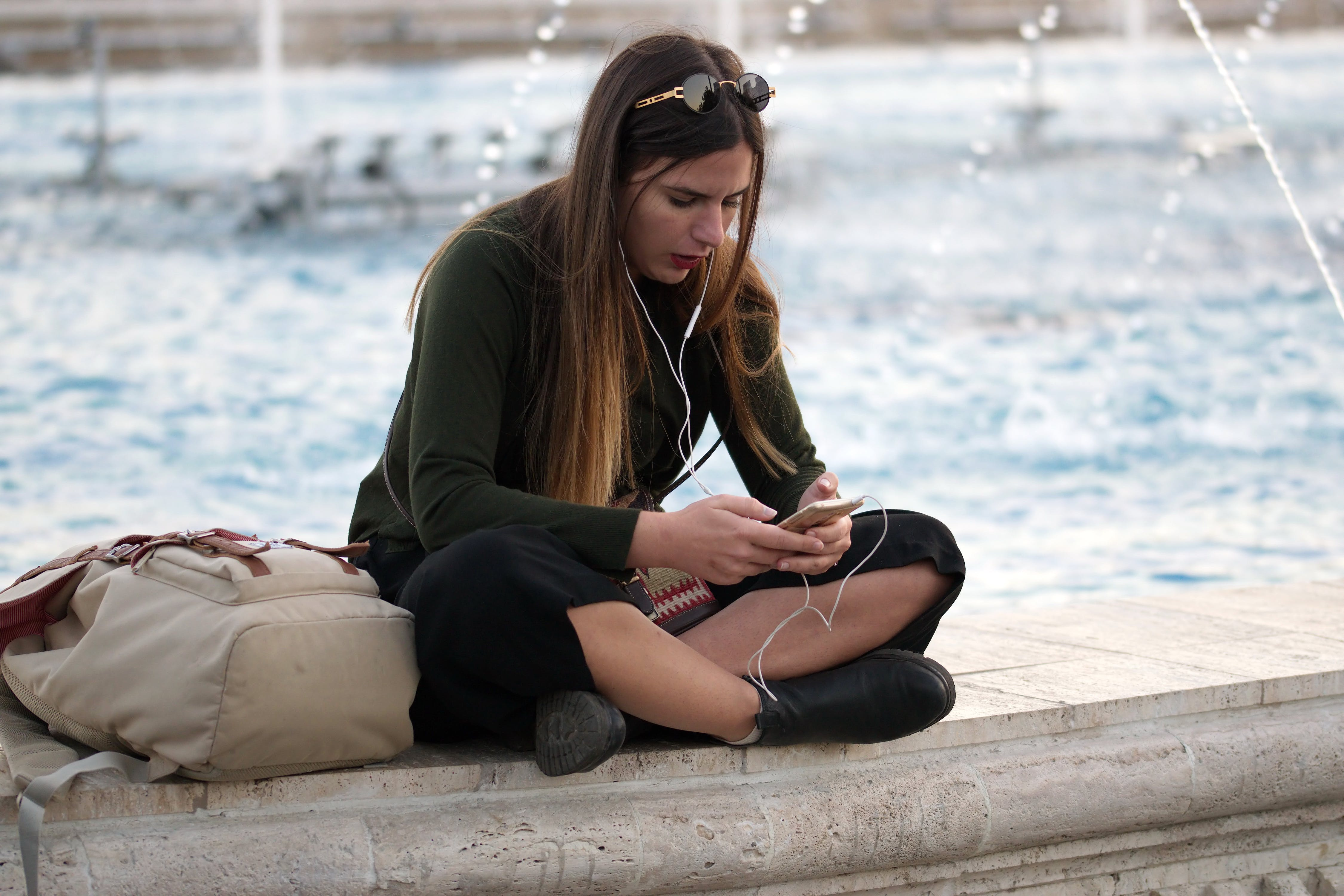 Woman Holding Smartphone While Sitting on Bench