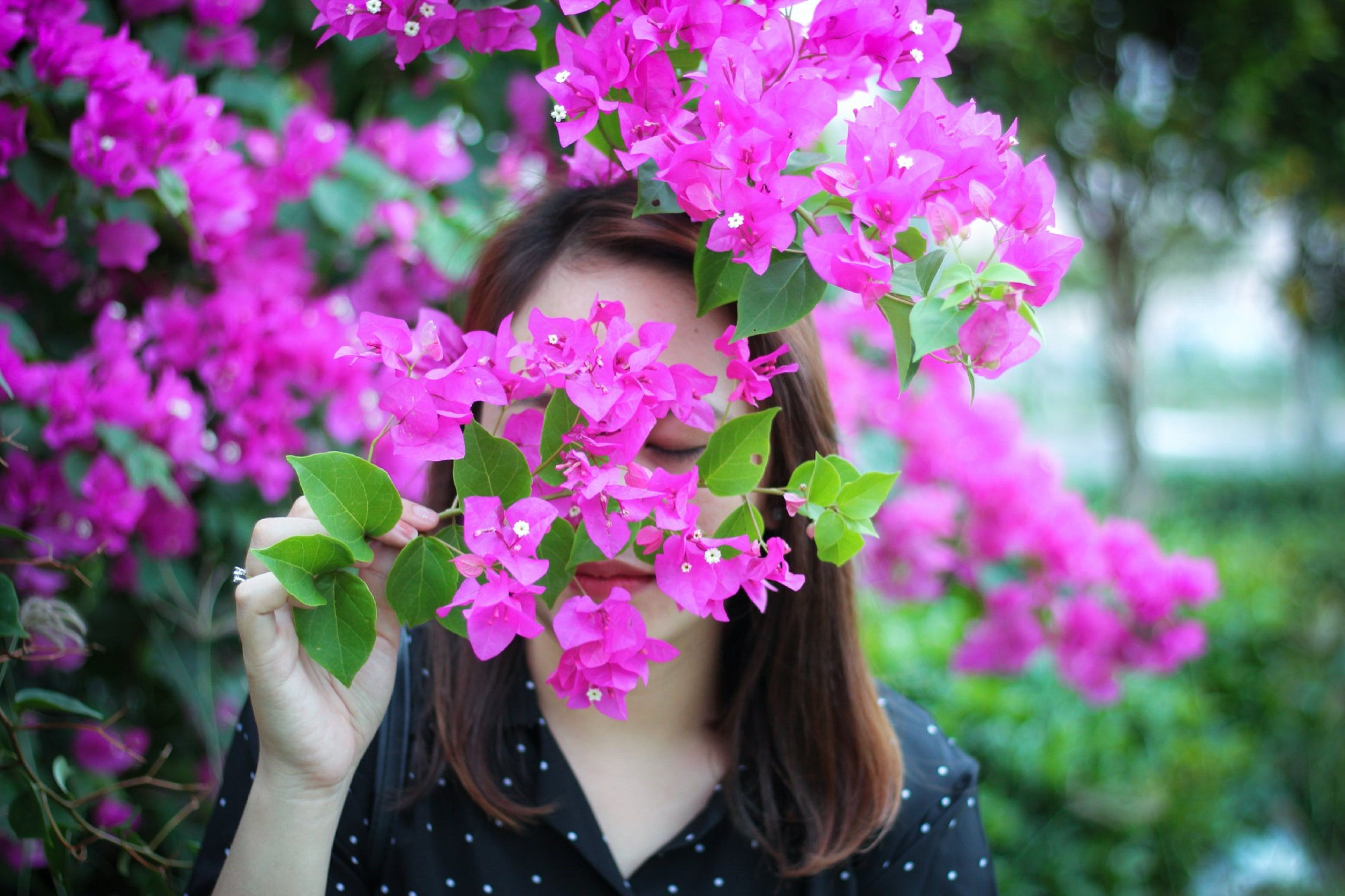 Photo of Woman Smelling Purple Flowers
